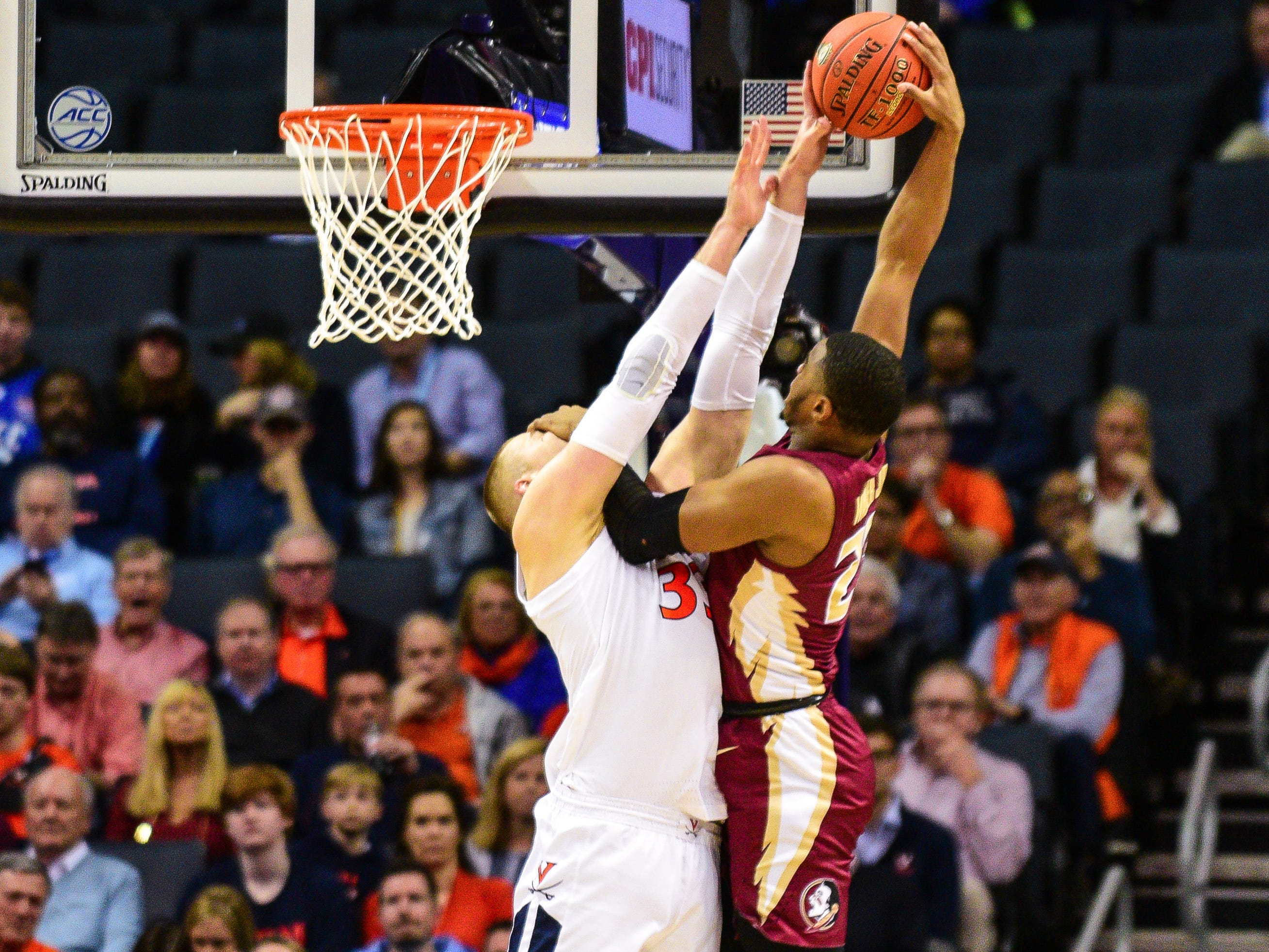 Florida State sophomore guard M.J. Walker attempts to dunk but is fouled by Virginia redshirt senior center Jack Salt during the first half of the ACC Tournament Semifinals at the Spectrum Center in Charlotte on Friday.