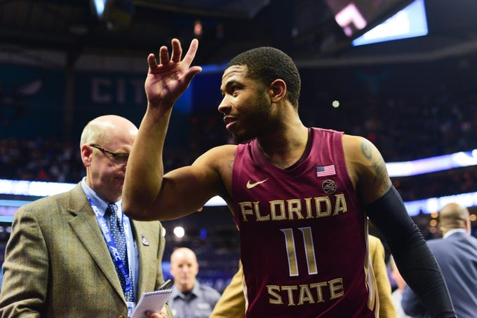 Senior guard David Nichols gestures cheering Florida State fans after the Seminoles 69-59 victory in the ACC Tournament Semifinal game at the Spectrum Center on Friday.
