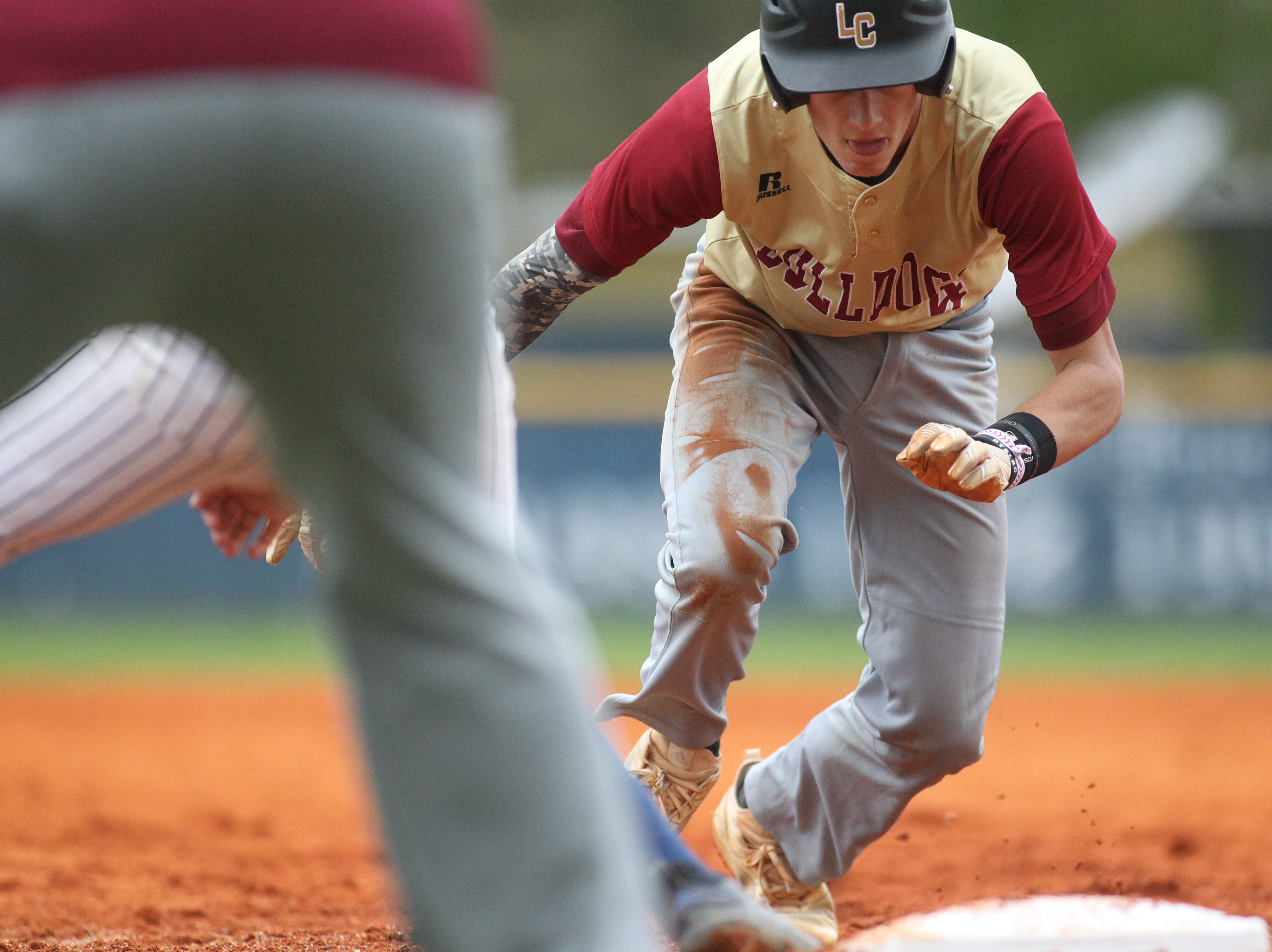 Liberty County's Austin Waller goes back to first on a pick-off attempt as Liberty County's baseball team went on the road to beat Maclay 8-2 on Saturday, March 16, 2019. The Bulldogs played their first game following their head coach Corey Crum's tragic death six days ago.