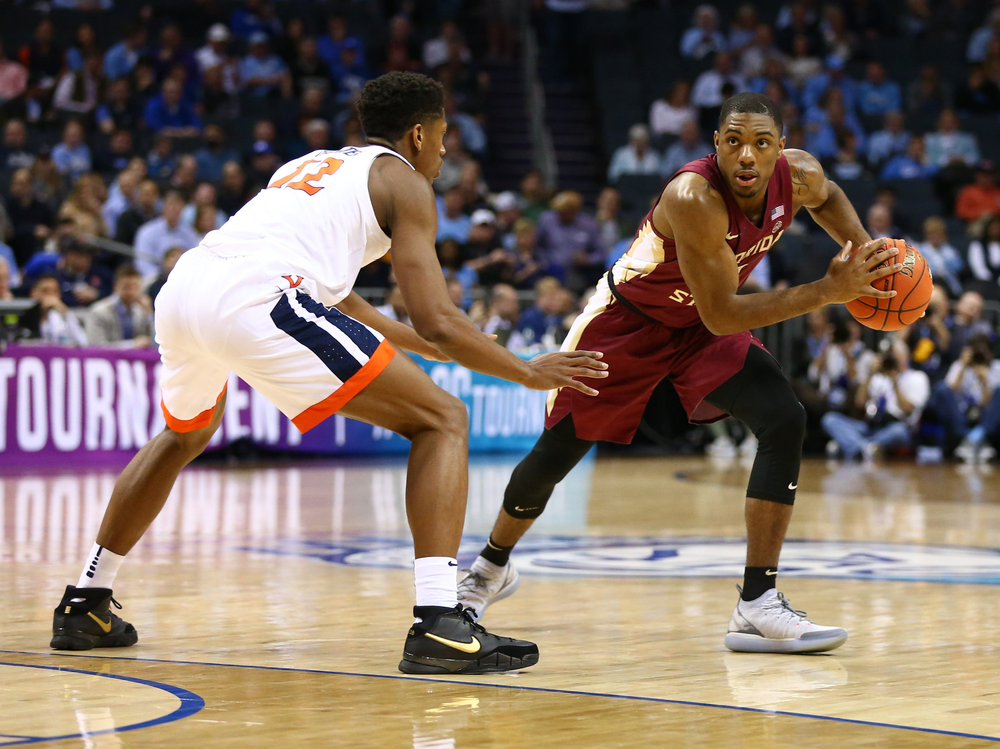 Mar 15, 2019; Charlotte, NC, USA; Florida State Seminoles guard Trent Forrest (3) sets up a play against Virginia Cavaliers guard De'Andre Hunter (12) in the first half in the ACC conference tournament at Spectrum Center. Mandatory Credit: Jeremy Brevard-USA TODAY Sports