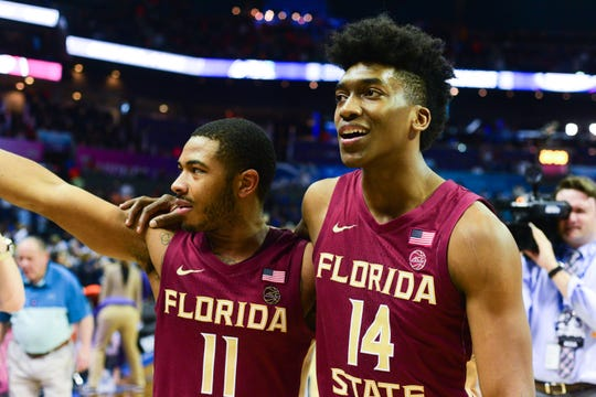Florida State senior guards David Nichols, left, and Terance Mann, right, celebrate the Seminoles 69-59 victory over Virginia in the ACC Semifinals at the Spectrum Center on Friday.