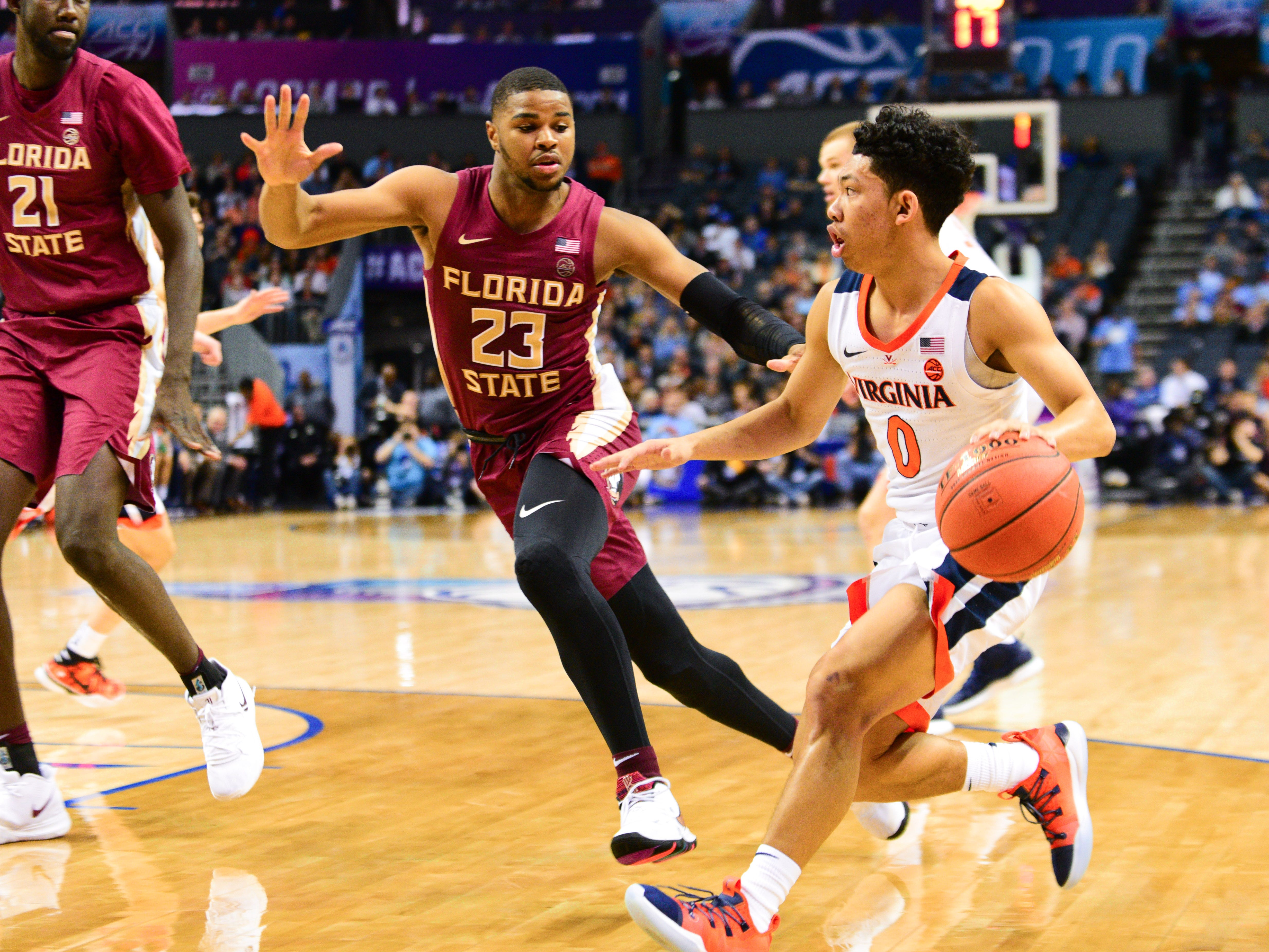 Florida State sophomore guard M.J. Walker, left, stops Virginia freshman guard Kihei Clark from advancing during the first half of the ACC Tournament Semifinals at the Spectrum Center in Charlotte on Friday.