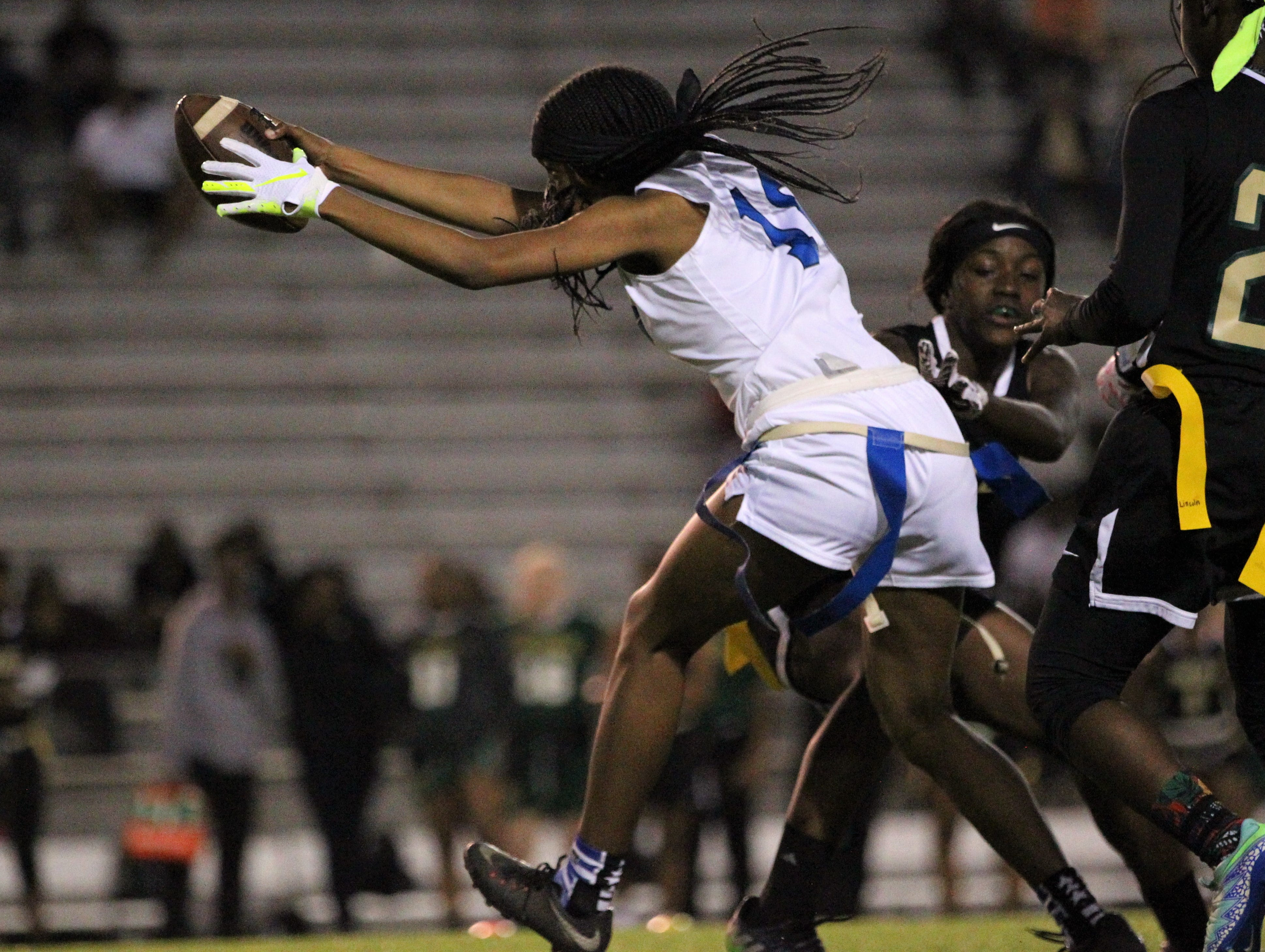 Godby's Gisele Jones reaches for extra yardage before her flag is pulled as Godby's flag football team beat Lincoln 25-6 at Gene Cox Stadium on March 14, 2019.