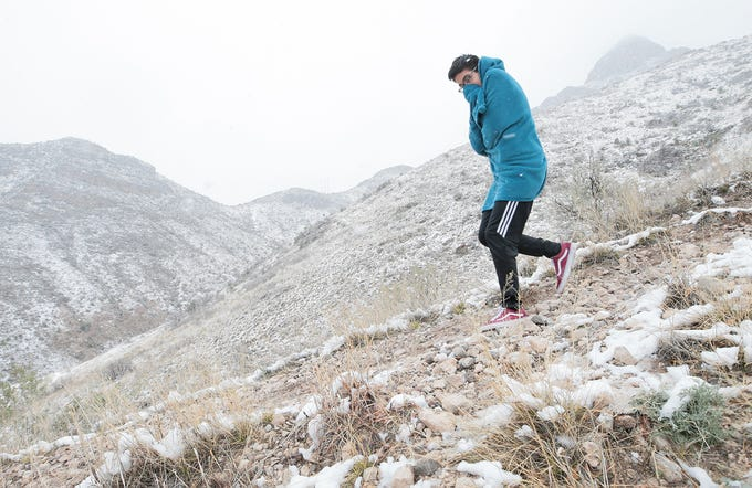 Carlos Cepeda, 13, tries to stay warm as he hikes the Franklin Mountains Saturday afternoon. Spring break began with a snowstorm in El Paso.