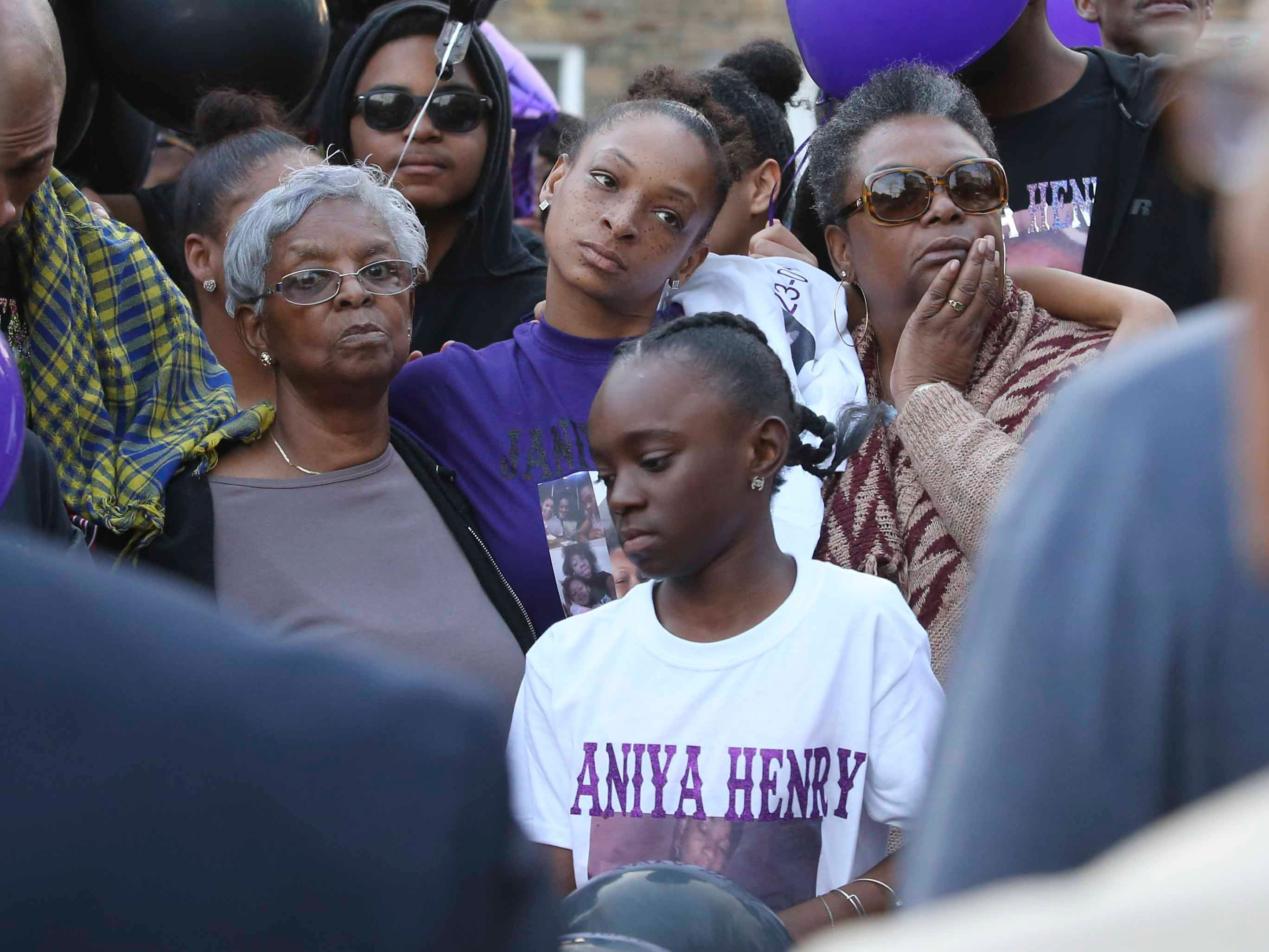 Shavontai Hale (center rear), mother of Janiya Henry, is flanked by her grandmother, Mamie Hale (left) and mother, Sheila Hale and other family members during a memorial gathering for Janiya Henry Friday evening in Wilmington.