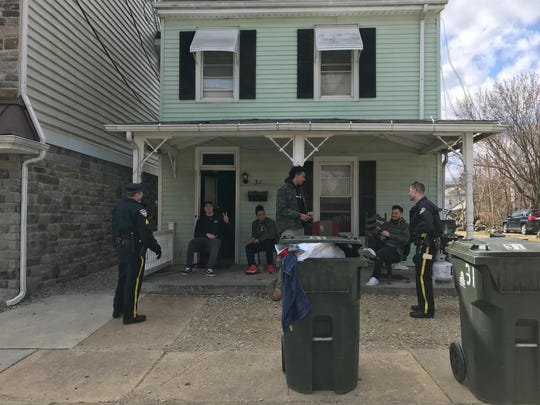 Students socialize with Newark police officers outside their house on Choate Street. Police emphasized gatherings like this were not the target of the new law.