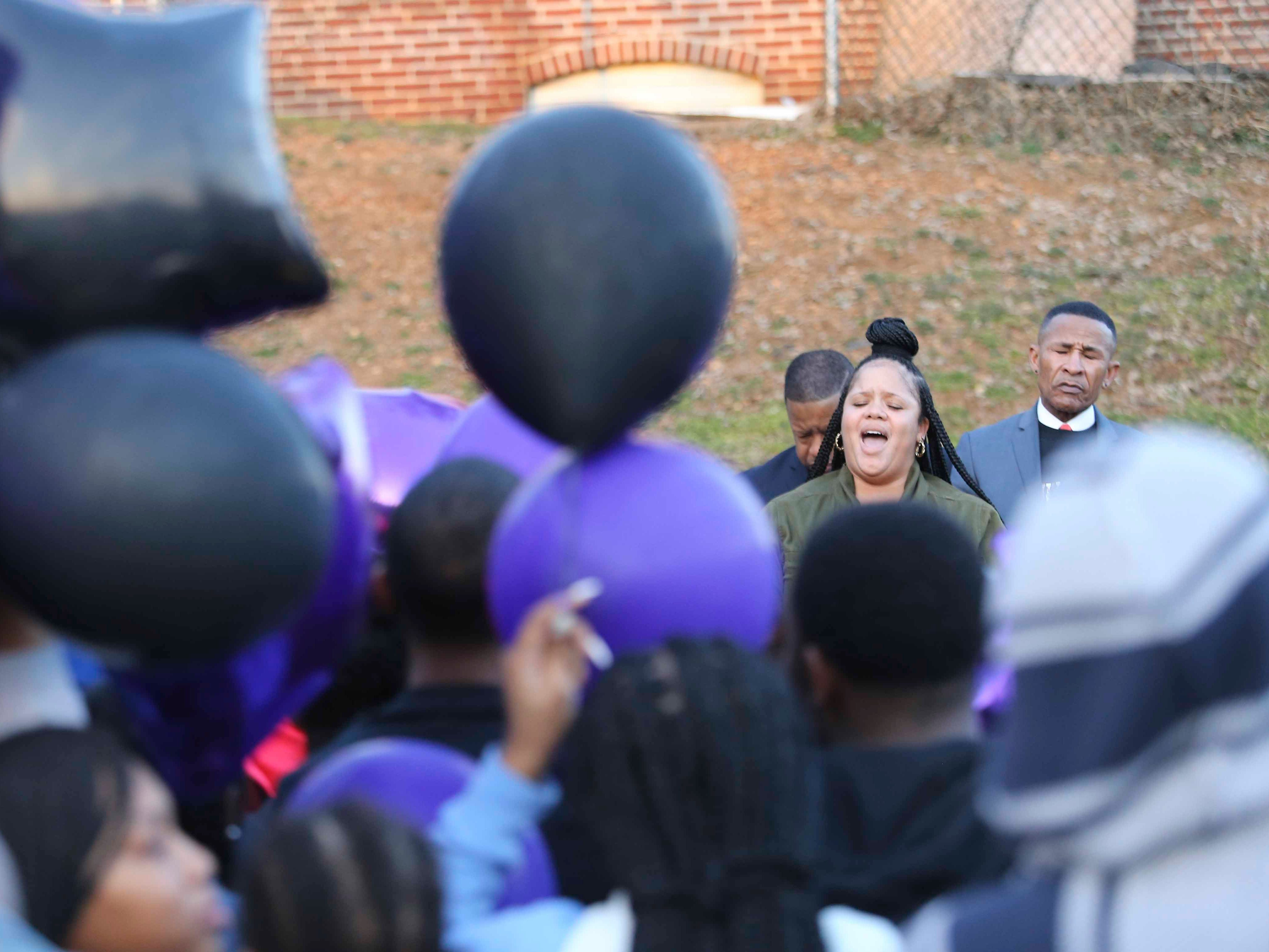 Shante Outlaw-Williams sings during a memorial gathering for Janiya Henry Friday evening after she and Christian Coffield were killed earlier this week in Wilmington