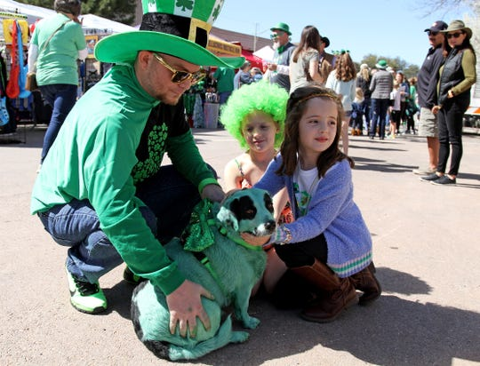 "In this file photo, Toby McClain and rescue dog Bandy meet Channing Davis and Harper Davenport, right, during the St. Patrick's Day festival. More Americans are viewing pets as a member of the family rather than ""just"" an animal."