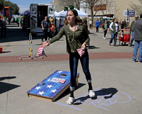 Jaycee Gentry plays cornhole during the St. Patrick's Day festival Saturday, March 16, 2019, in downtown Wichita Falls.