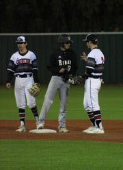 Rider's Jerry Montijo chats with Old High's Jacob Weaver (left) and Zach Williams (right) at second base. Rider defeated Old High 6-2 at Hoskins Field Friday, March 15, 2019.