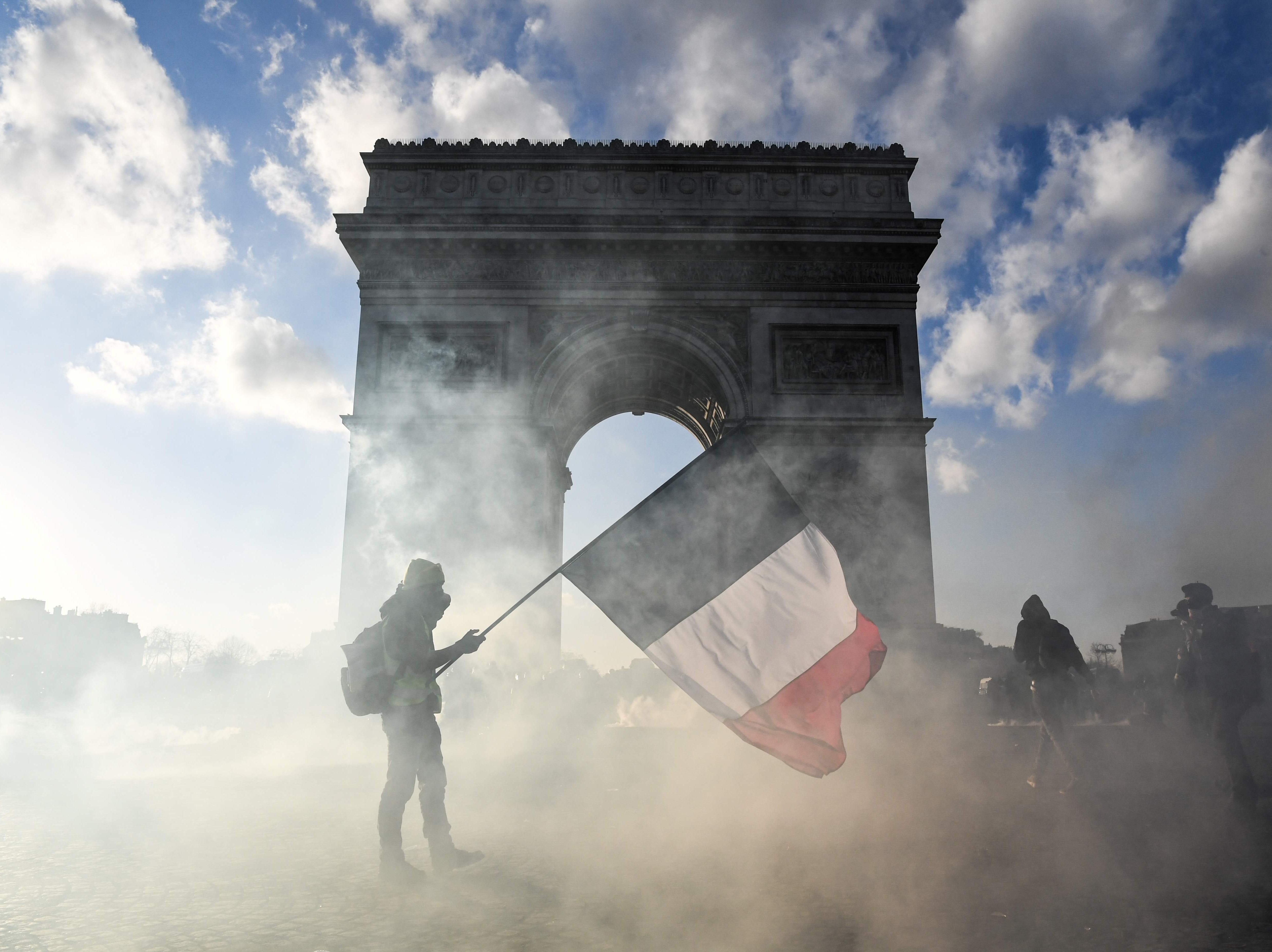 A protester holds a French national flag as he walks among tear gas smoke past the Arc de Triomphe on the Place de l'Etoile in Paris on March 16, 2019, during clashes between Yellow Vest protesters and riot police forces, on the 18th consecutive Saturday of demonstrations called by the 'Yellow Vest' (gilets jaunes) movement.
