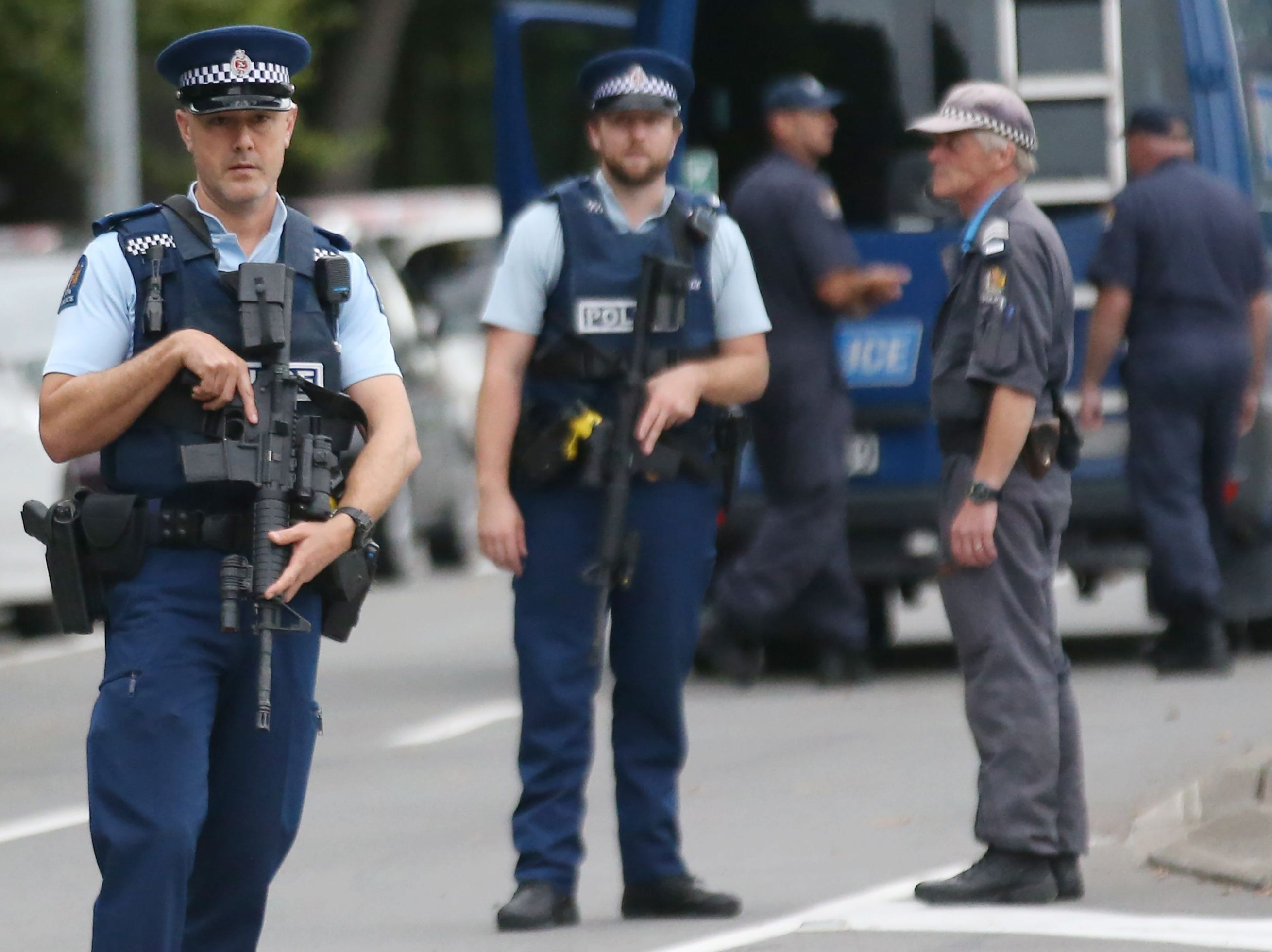 Armed police keep watch as people pay their respects in front of floral tributes for victims of the March 15 mosque attacks, in Christchurch on March 16, 2019.