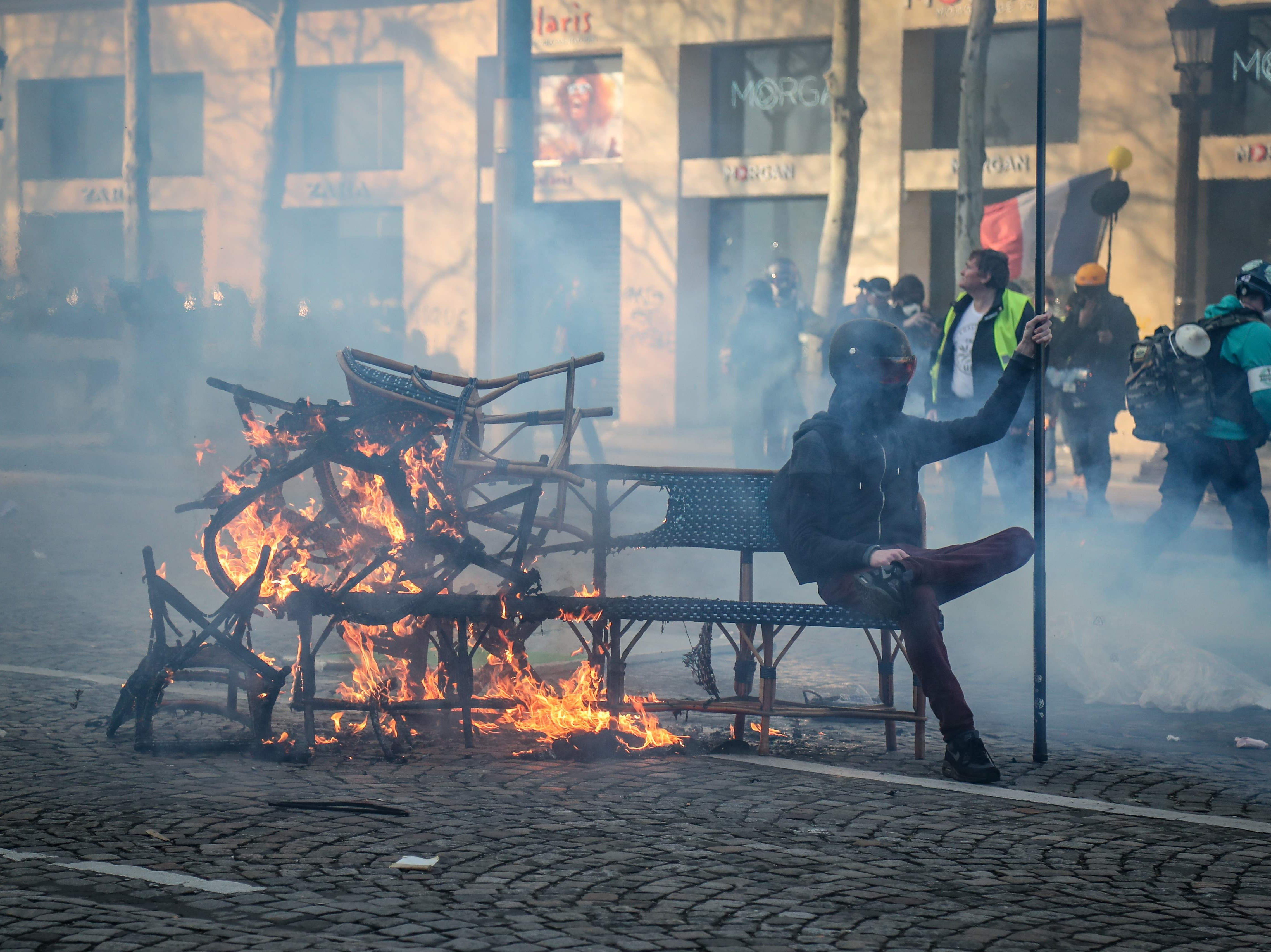 A protester sits on a bench part of a burning barricade of restaurant chairs on the Champs-Elysees in Paris on March 16, 2019, during clashes between riot police forces and Yellow Vest protesters on the 18th consecutive Saturday of demonstrations called by the 'Yellow Vest' (gilets jaunes) movement.