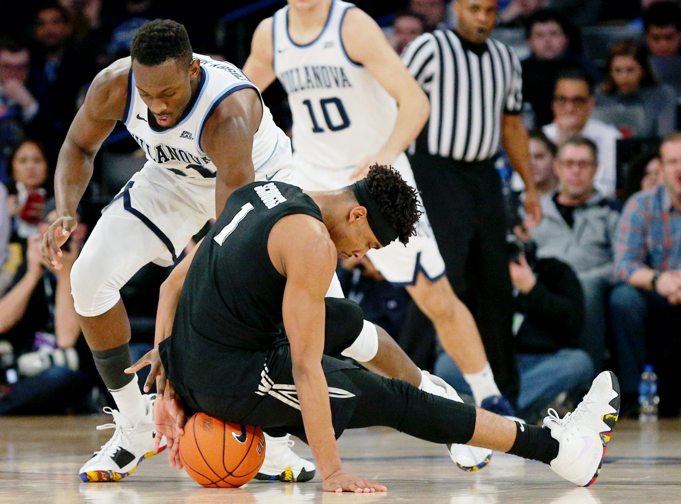 March 15: Xavier Musketeers guard Paul Scruggs (1) and Villanova Wildcats forward Dhamir Cosby-Roundtree (21) scramble for the ball during the first half of a Big East tournament game.