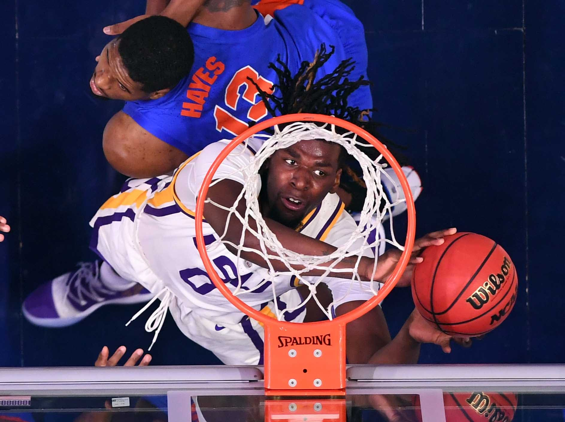 March 15: LSU Tigers forward Naz Reid (0) puts in a rebound behind pressure from Florida Gators center Kevarrius Hayes (13) in the SEC tournament.