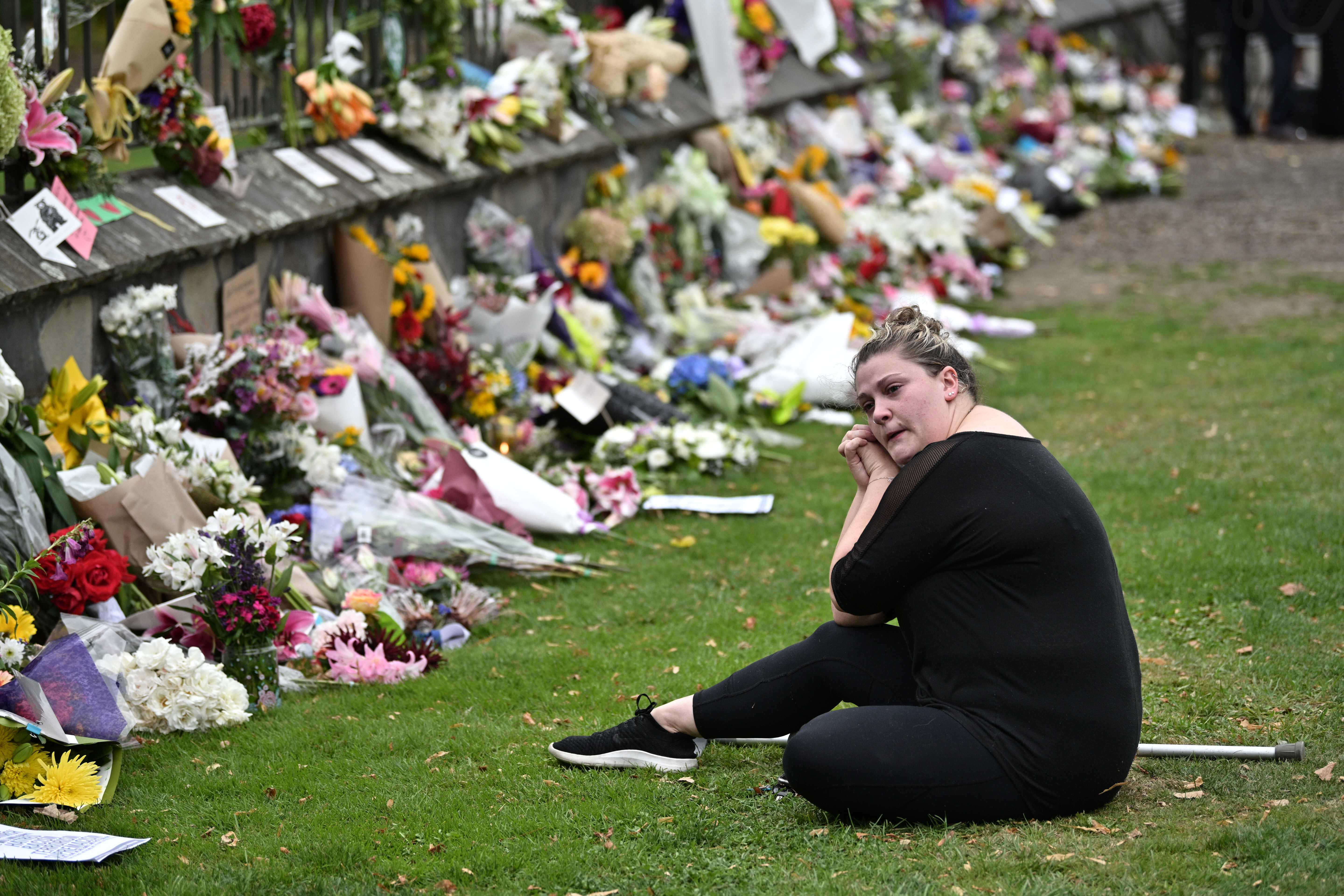 A woman reacts as she sits among flowers left in tribute to victims outside the entrance of the hospital in Christchurch on March 16, 2019, after a shooting incident at two mosques in Christchurch the previous day.