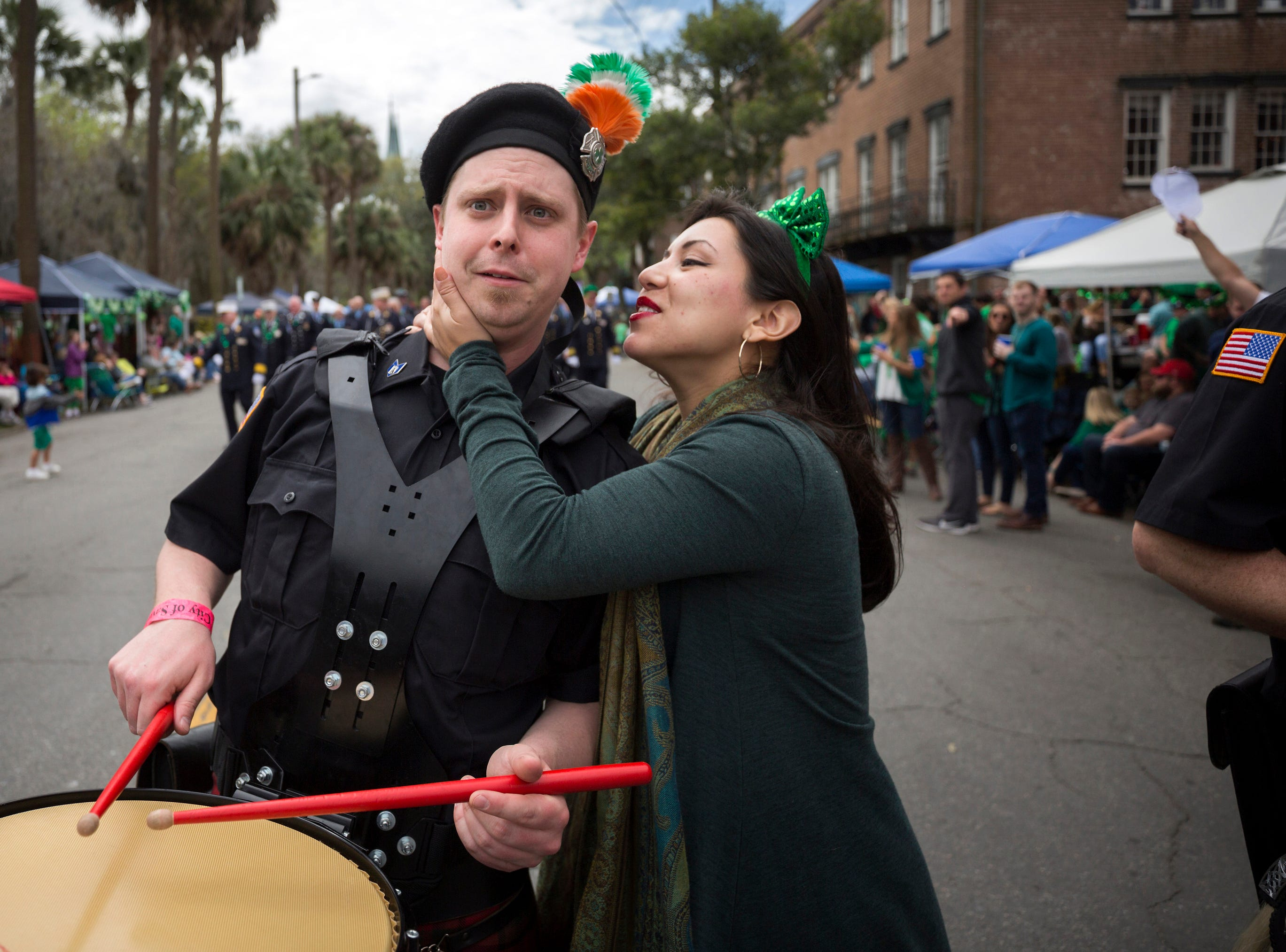 A Yonkers Fire Pipe and Drum drummer reacts to being kissed by Kayla DeJesus, right, while he marches in the 195-year-old Savannah St. Patrick's Day parade, Saturday, March 16, 2019, in Savannah, Ga.
