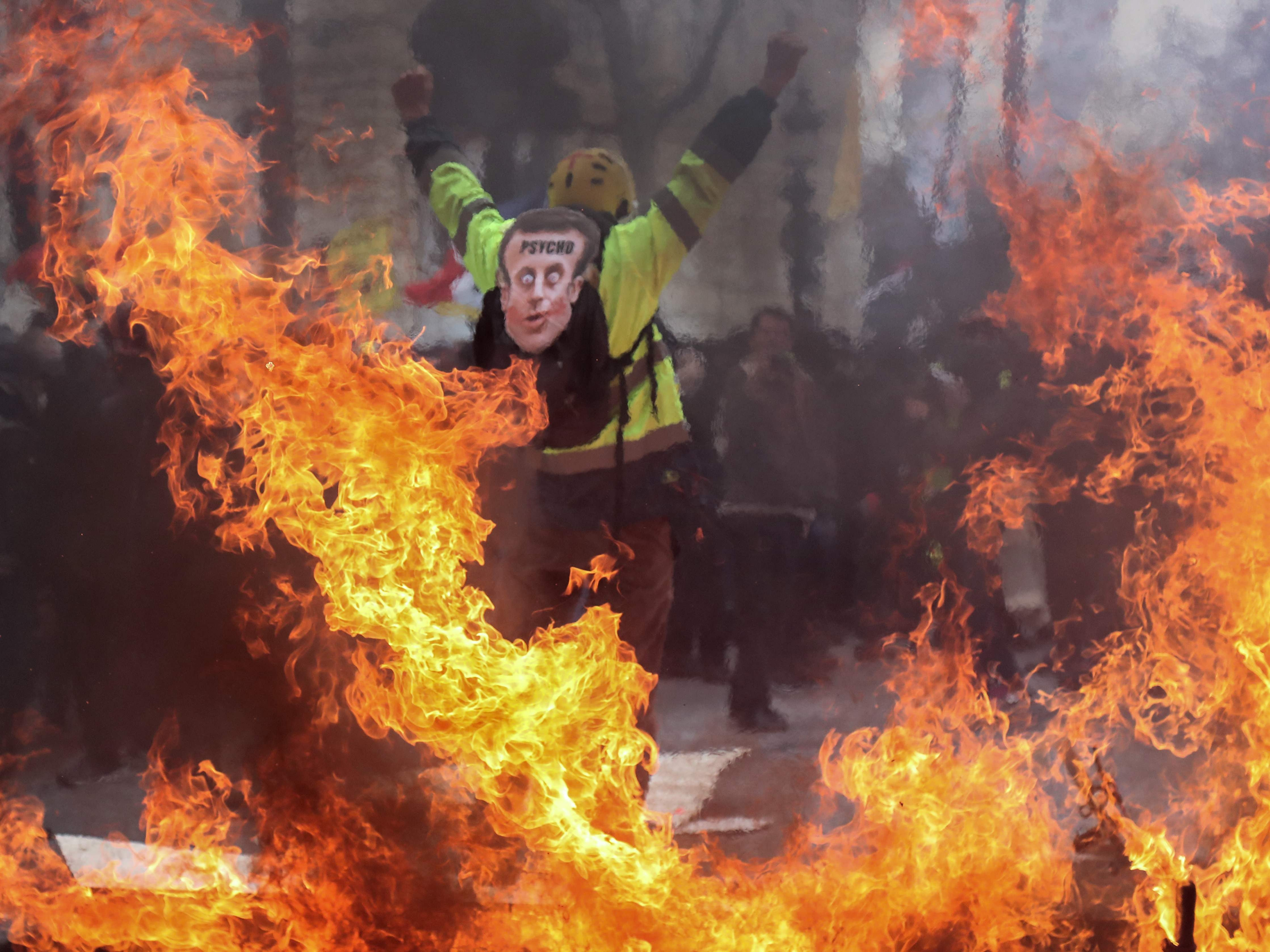 A Yellow Vest protester wearing a mask depicting the French President gestures behind flames rising from barricades, in Paris on March 16, 2019, during the 18th consecutive Saturday of demonstrations called by the 'Yellow Vest' (gilets jaunes) movement.