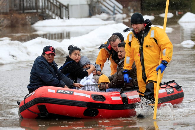 Green Bay firefighters assist residents in evacuating their homes due to the East river flooding on Friday, March 15, 2019 in Green Bay, Wis. Heavy rain falling atop deeply frozen ground has prompted evacuations along swollen rivers in Wisconsin, Nebraska and other Midwestern states, while powerful wind and snow has impacted hundreds of miles of interstates in North Dakota. (Adam Wesley/The Post-Crescent via AP) ORG XMIT: WIAPP505