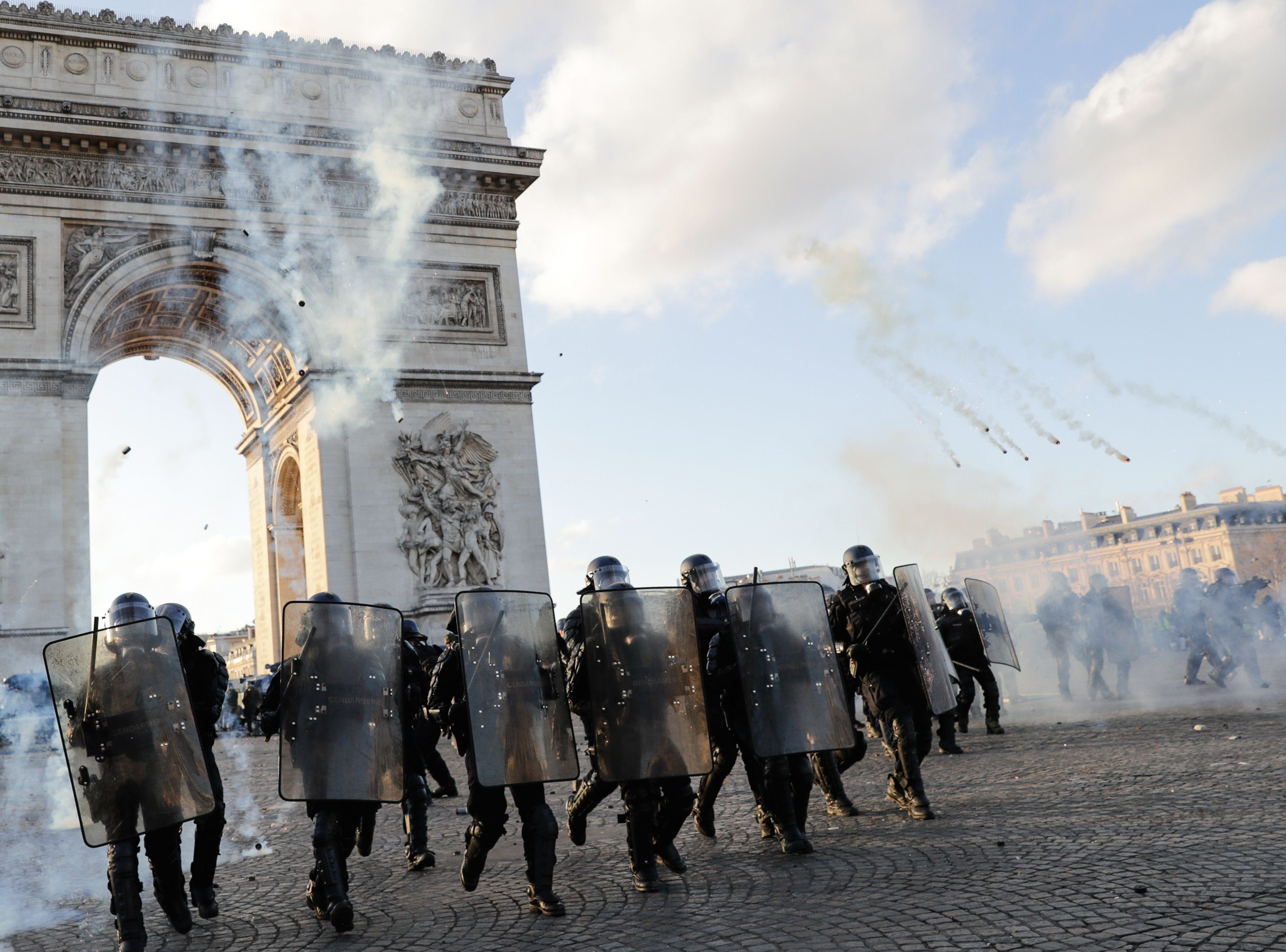 Riot police charge using tear gas canister at the Arc de Triomphe on the Place de l'Etoile in Paris on March 16, 2019, during clashes with Yellow Vest protesters, on the 18th consecutive Saturday of demonstrations called by the 'Yellow Vest' (gilets jaunes) movement.
