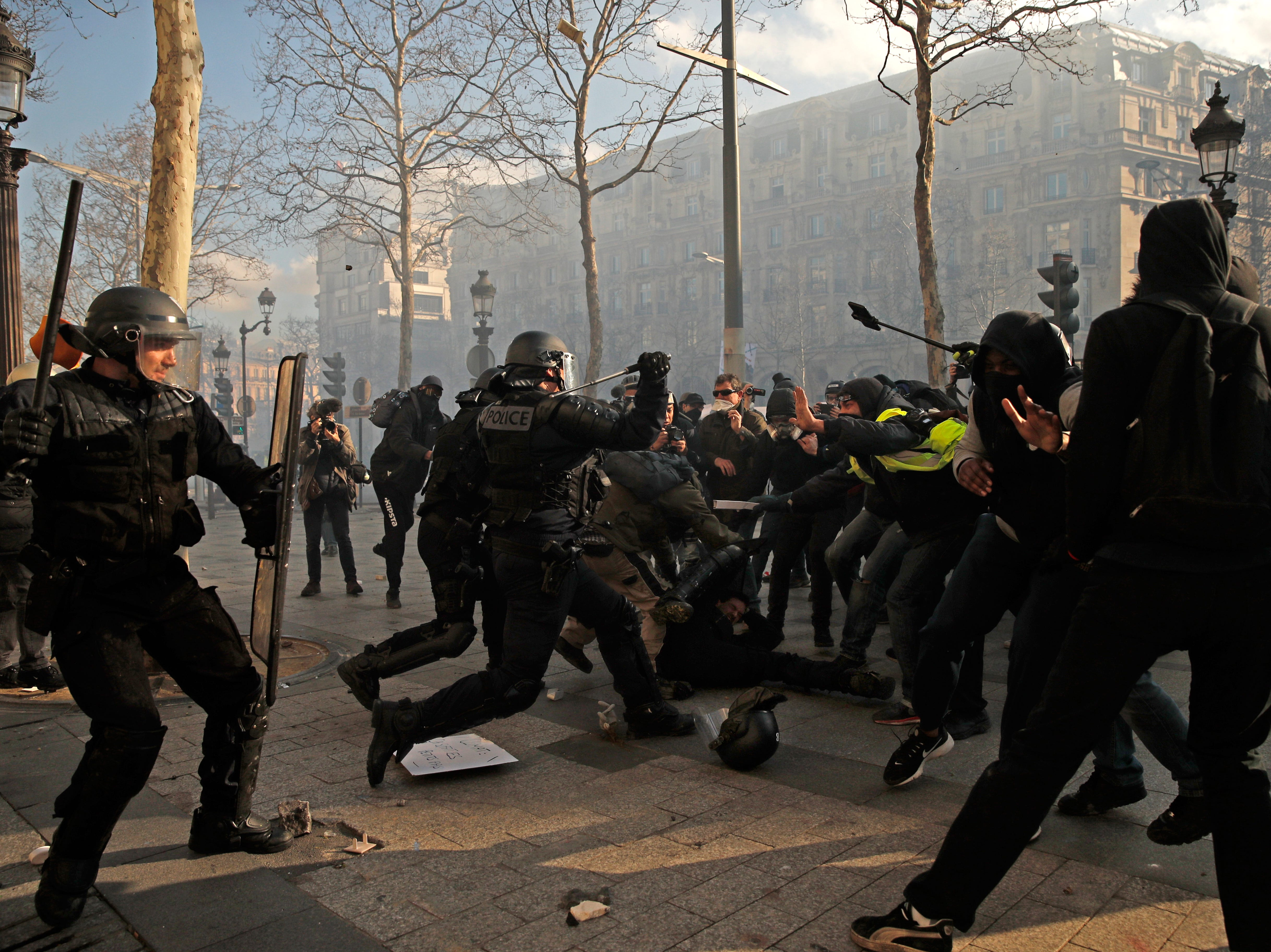 Yellow Vests protesters hit a riot police officer on the Champs Elysees during the 'Act XVIII' demonstration in Paris, France, 16 March 2019.