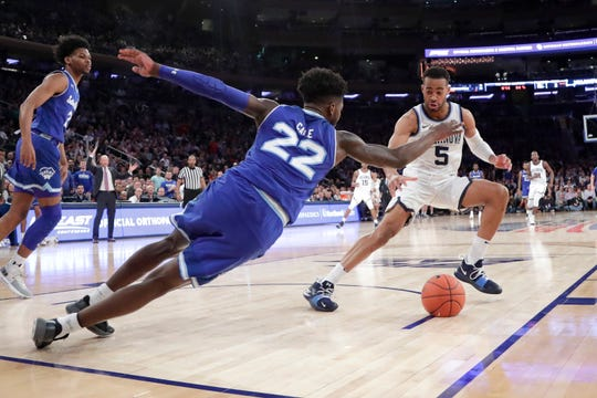 Seton Hall guard Myles Cale (22) and Villanova guard Phil Booth (5) compete for a loose ball