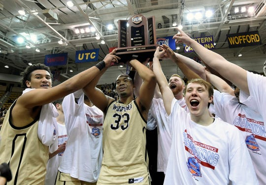 Wofford Keve Aluma, left, Cameron Jackson (33), Storm Murphy (5), right, and teammates celebrate their win over UNC-Greensboro for the NCAA college basketball Southern Conference tournament championship