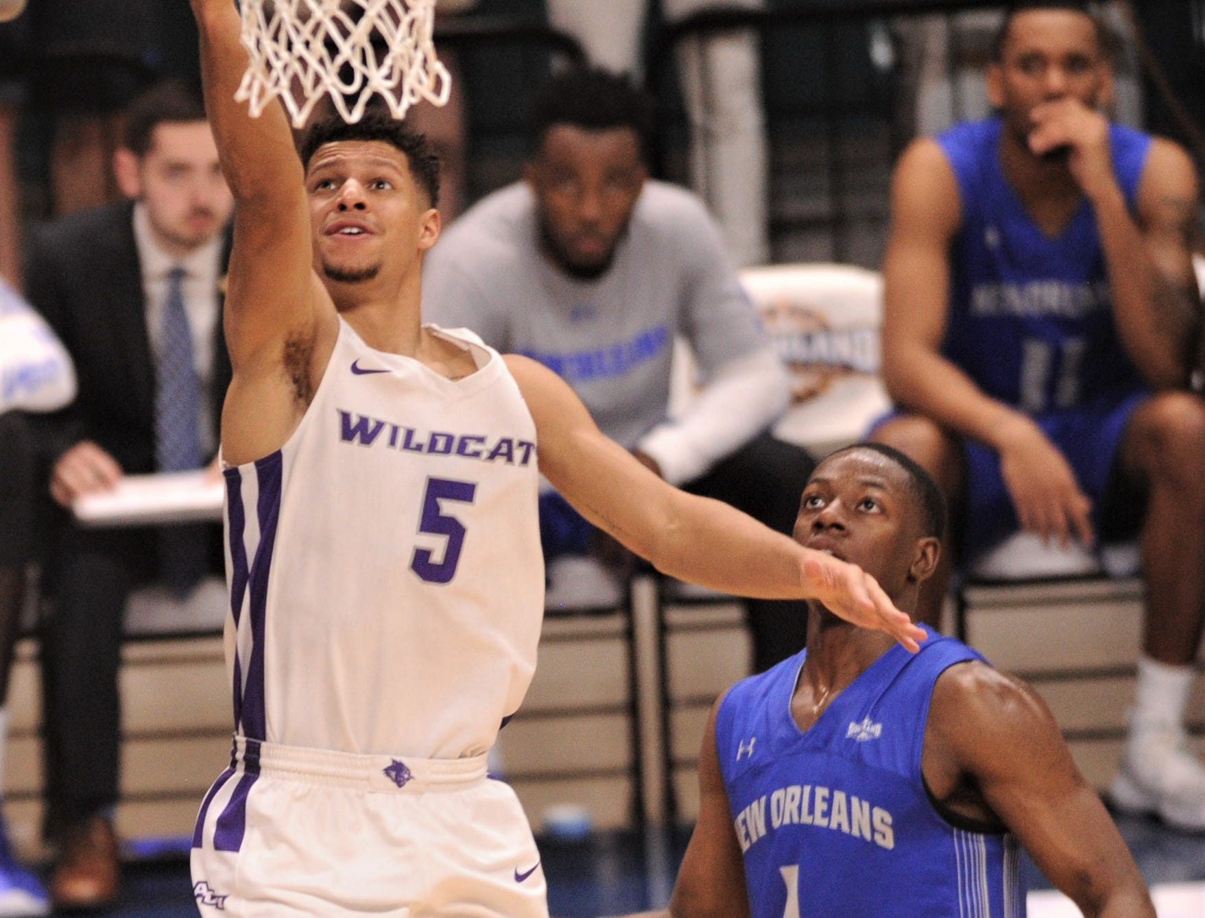 ACU's Payten Ricks, left, drives to the basket as New Orleans' Damion Rosser looks on. ACU beat the Privateers 77-60 to win the Southland Conference Tournament title Saturday, March 16, 2019, at the Merrell Center in Katy.