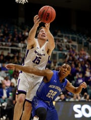 Abilene Christian forward Hayden Farquhar (15) reaches for a rebound over New Orleans guard Larry Robinson III (20) during the first half of an NCAA college basketball game for the Southland Conference men's tournament title Saturday.