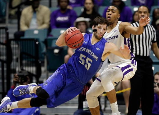 New Orleans forward Scott Plaisance Jr. (55) slips as he attempts to drive around Abilene Christian forward Jaren Lewis during the first half of Saturday's game in Katy.