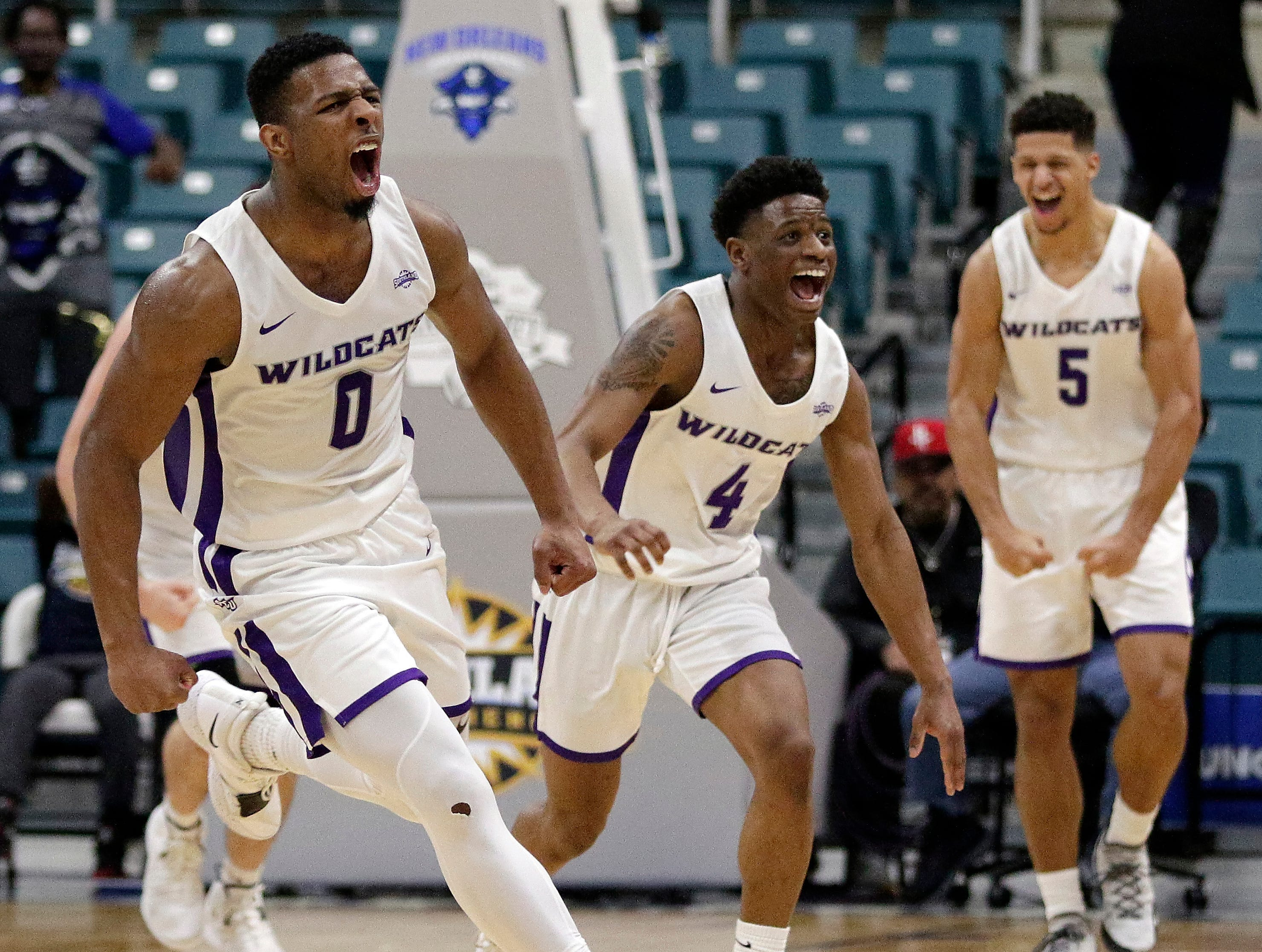 Abilene Christian guard Jaylen Franklin (0), guard Damien Daniels (4) and guard Payten Ricks (5) celebrate the team's lead in the final minute of an NCAA college basketball game against New Orleans for the Southland Conference men's tournament title Saturday, March 16, 2019, in Katy, Texas.