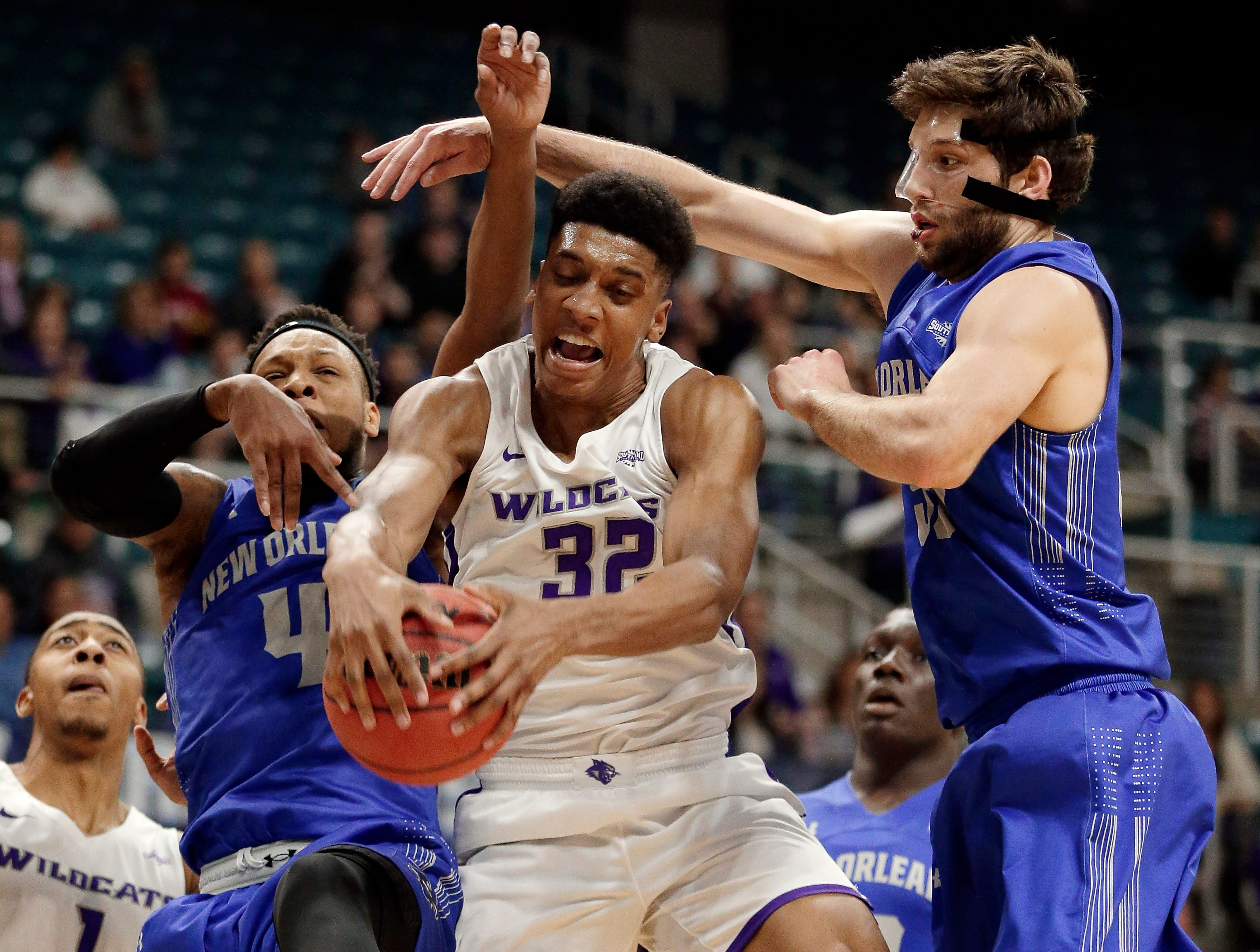 Abilene Christian forward Joe Pleasant (32) pulls in a rebound between New Orleans guard Bryson Robinson (4) and forward Scott Plaisance Jr., right, during the first half of an NCAA college basketball game for the Southland Conference men's tournament title Saturday, March 16, 2019, in Katy, Texas.