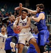 Abilene Christian forward Joe Pleasant (32) pulls in a rebound between New Orleans guard Bryson Robinson (4) and forward Scott Plaisance Jr., right, during the first half of Saturday's title game.