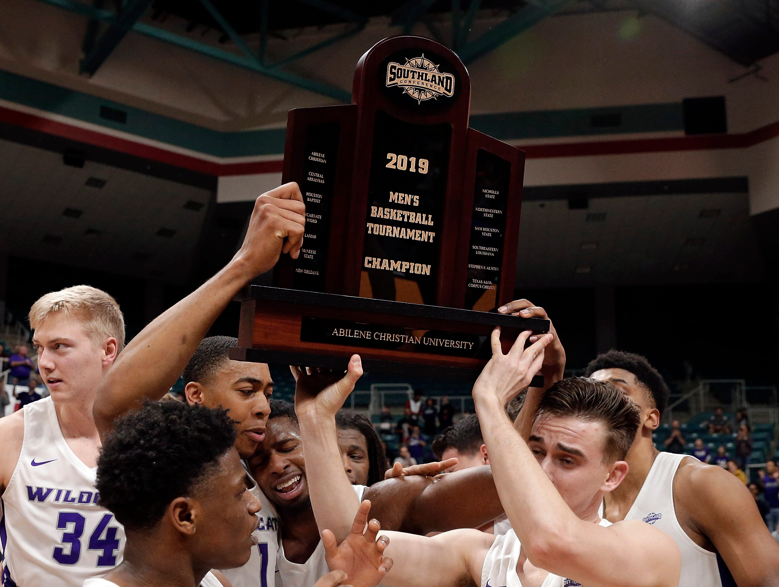Abilene Christian players hoist the championship trophy after defeating New Orleans in an NCAA college basketball game for the Southland Conference men's tournament title Saturday, March 16, 2019, in Katy, Texas.