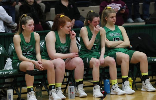 Seton Catholic players watch from the bench as Mendon players celebrate their 59-50 victory in the girls Class A state championship game at Hudson Valley Community College in Troy March 17, 2019.