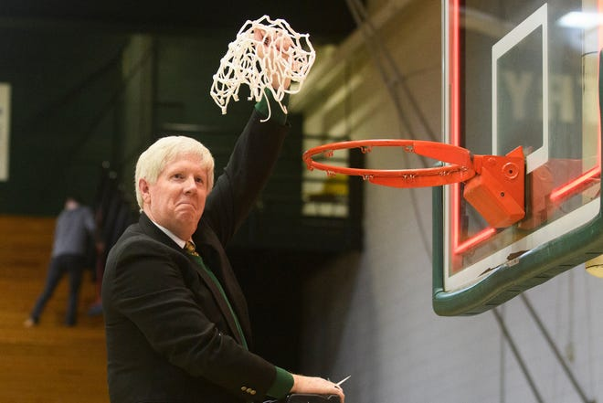 St. Johnsbury head coach David McGinn celebrates after cutting down the net during the DI boys basketball championship game between the St. Johnsbury Hilltoppers and the Rutland Raiders at Patrick Gym on Sunday afternoon March 17, 2019 in Burlington, Vermont.