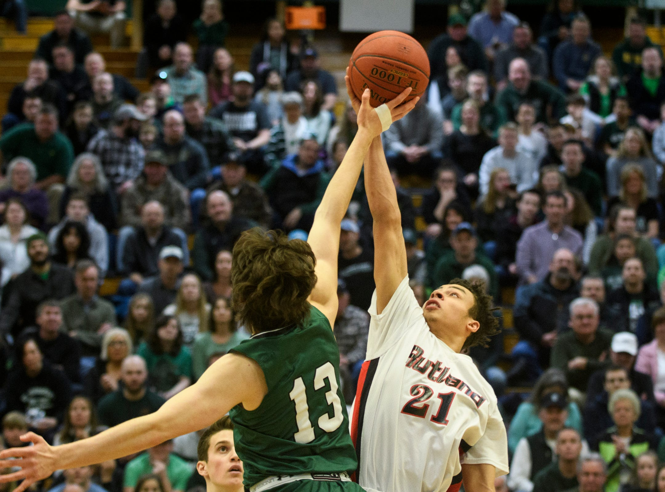 Rutland's Jamison Evans (21) and St. Johnsbury's Alex Carlisle (13) battle for the opening tip off during the DI boys basketball championship game between the St. Johnsbury Hilltoppers and the Rutland Raiders at Patrick Gym on Sunday afternoon March 17, 2019 in Burlington, Vermont.