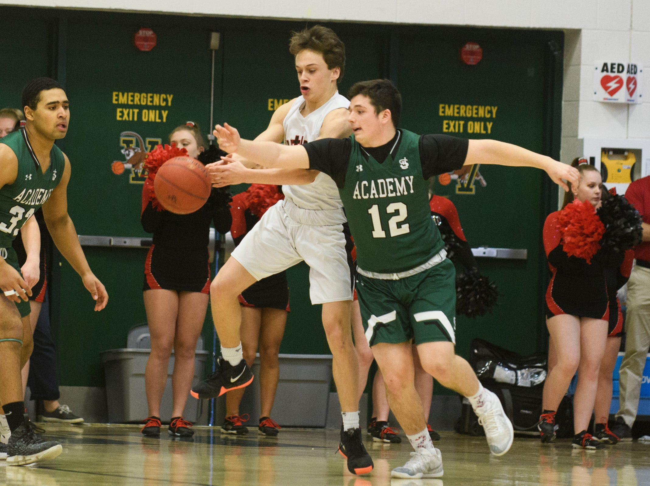 St. Johnsbury's Nic Guckin (12) battles for the loose ball with Rutland's Eric Coughlin (20) during the DI boys basketball championship game between the St. Johnsbury Hilltoppers and the Rutland Raiders at Patrick Gym on Sunday afternoon March 17, 2019 in Burlington, Vermont.