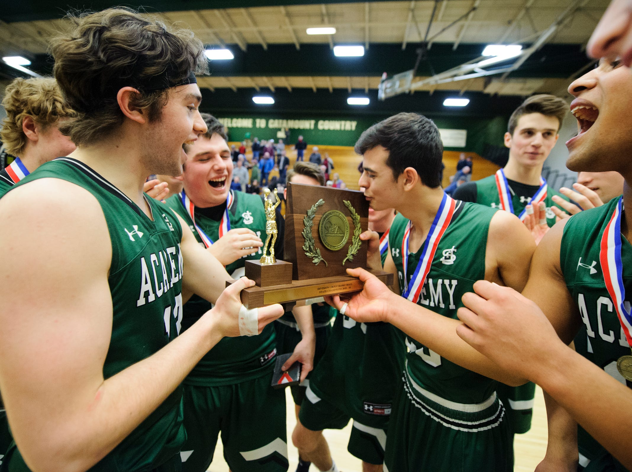 St. Johnsbury celebrates with the championship trophy during the DI boys basketball championship game between the St. Johnsbury Hilltoppers and the Rutland Raiders at Patrick Gym on Sunday afternoon March 17, 2019 in Burlington, Vermont.