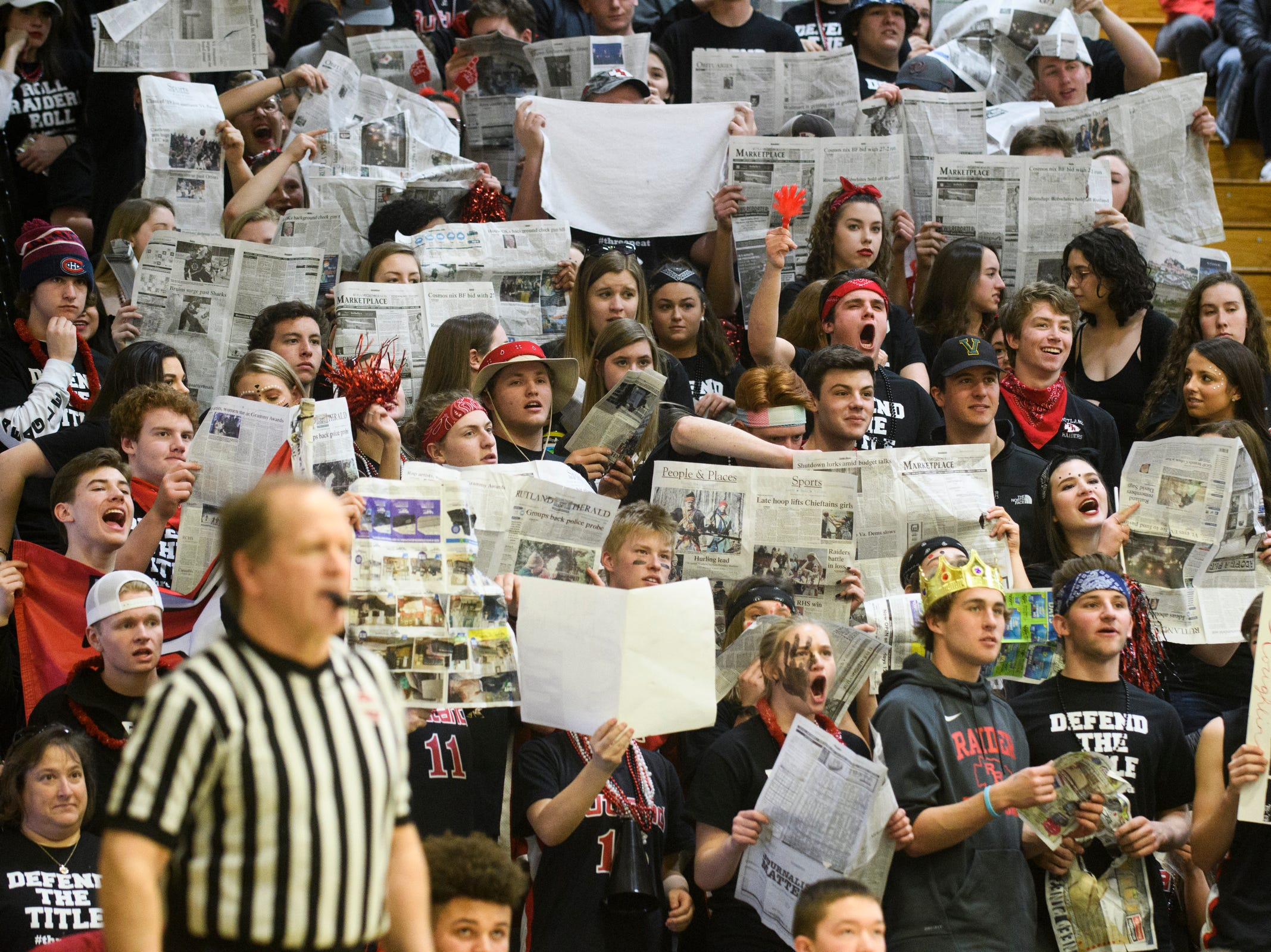 Rutland fans hold p newspapers during the DI boys basketball championship game between the St. Johnsbury Hilltoppers and the Rutland Raiders at Patrick Gym on Sunday afternoon March 17, 2019 in Burlington, Vermont.