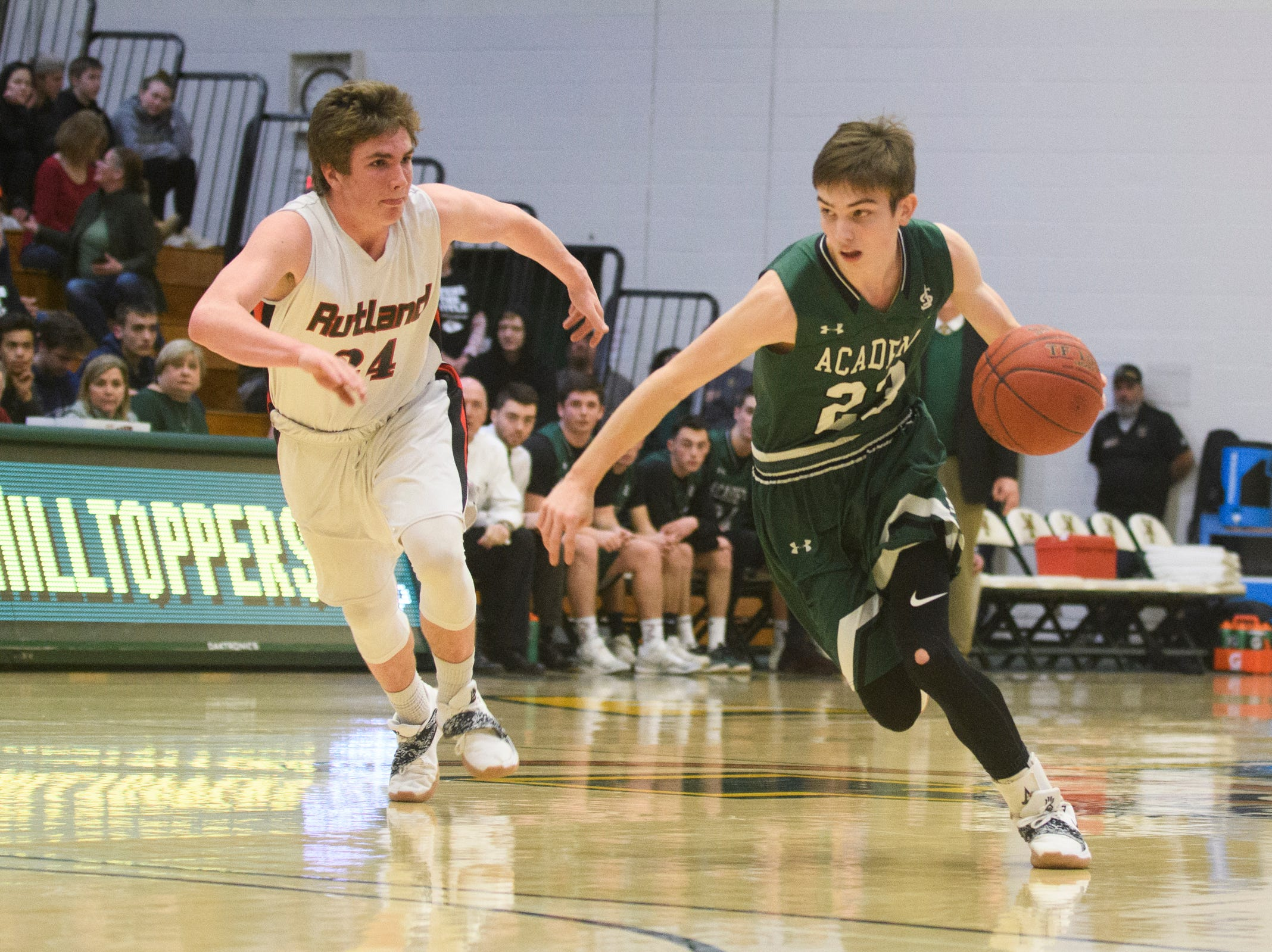 St. Johnsbury's Logan Wendell (23) drives to the hoop past Rutland's Jacob Lorman (24) during the DI boys basketball championship game between the St. Johnsbury Hilltoppers and the Rutland Raiders at Patrick Gym on Sunday afternoon March 17, 2019 in Burlington, Vermont.