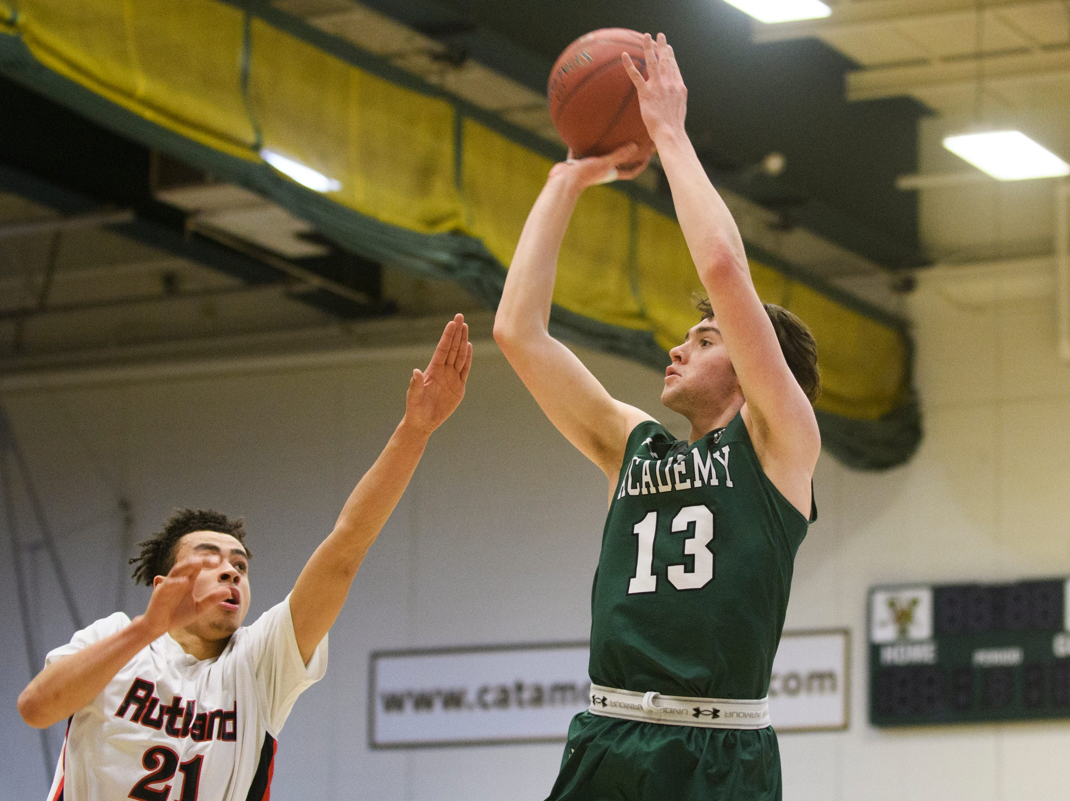 St. Johnsbury's Alex Carlisle (13) shoots the ball over Rutland's Jamison Evans (21) during the DI boys basketball championship game between the St. Johnsbury Hilltoppers and the Rutland Raiders at Patrick Gym on Sunday afternoon March 17, 2019 in Burlington, Vermont.