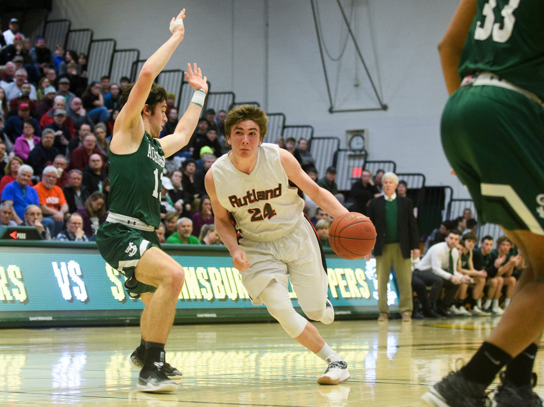 Rutland's Jacob Lorman (240 drives to the hoop past St. Johnsbury's Alex Carlisle (13) during the DI boys basketball championship game between the St. Johnsbury Hilltoppers and the Rutland Raiders at Patrick Gym on Sunday afternoon March 17, 2019 in Burlington, Vermont.