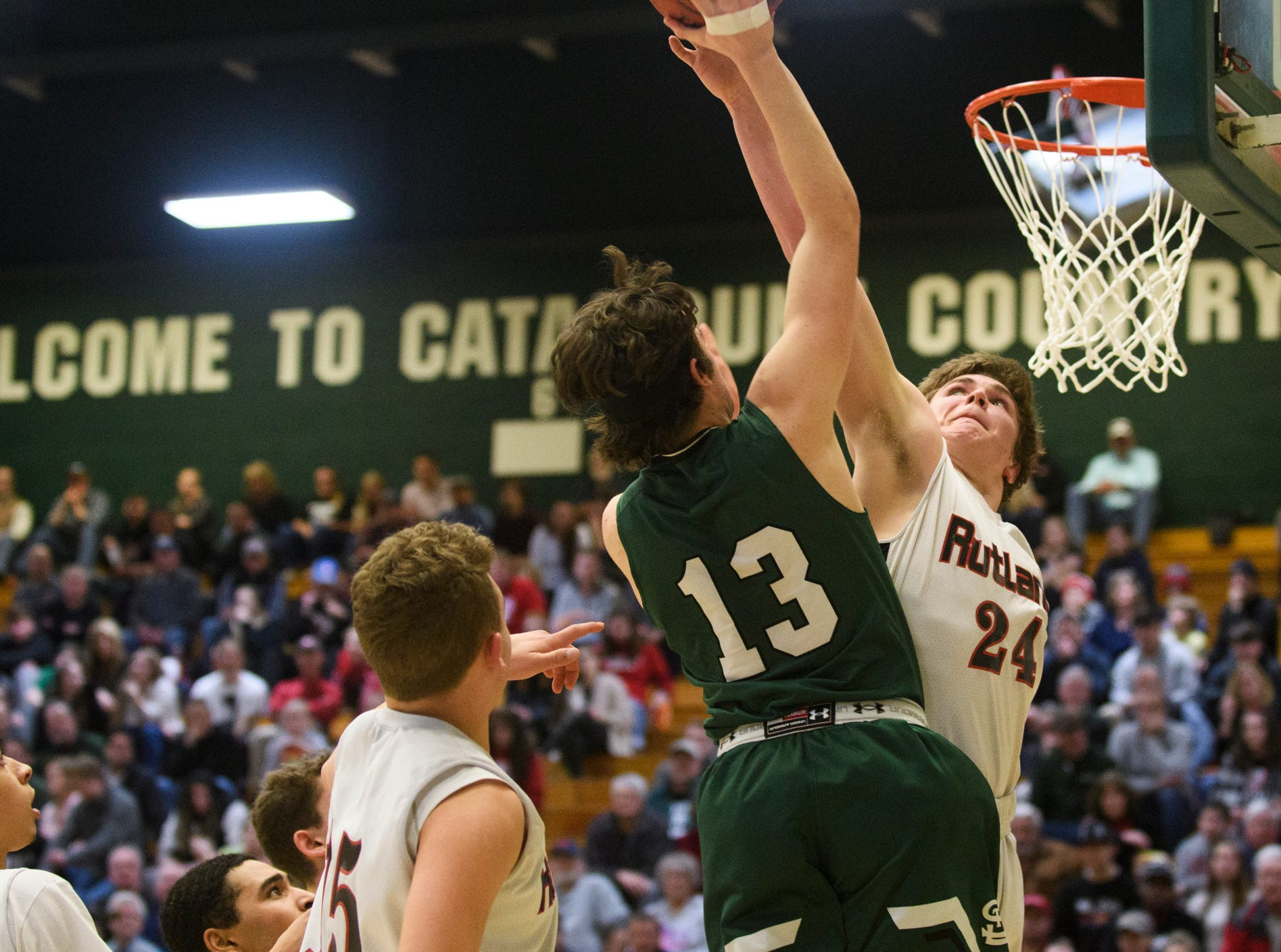 St. Johnsbury's Alex Carlisle (13) leaps to shoot the ball over Rutland's Jacob Lorman (24) during the DI boys basketball championship game between the St. Johnsbury Hilltoppers and the Rutland Raiders at Patrick Gym on Sunday afternoon March 17, 2019 in Burlington, Vermont.