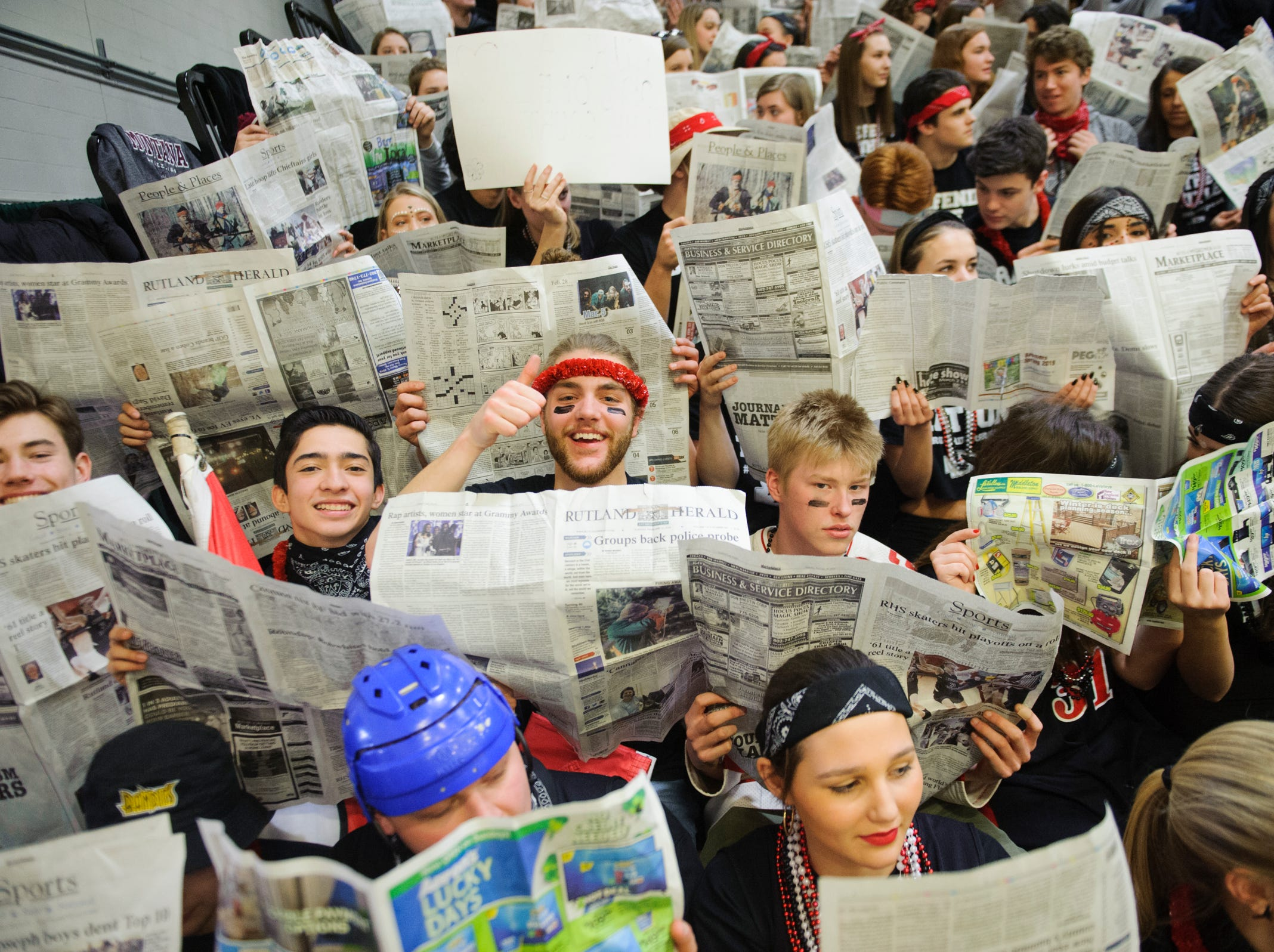 Rutland fans hold up newspapers as St. Johnsbury is introduced during the DI boys basketball championship game between the St. Johnsbury Hilltoppers and the Rutland Raiders at Patrick Gym on Sunday afternoon March 17, 2019 in Burlington, Vermont.