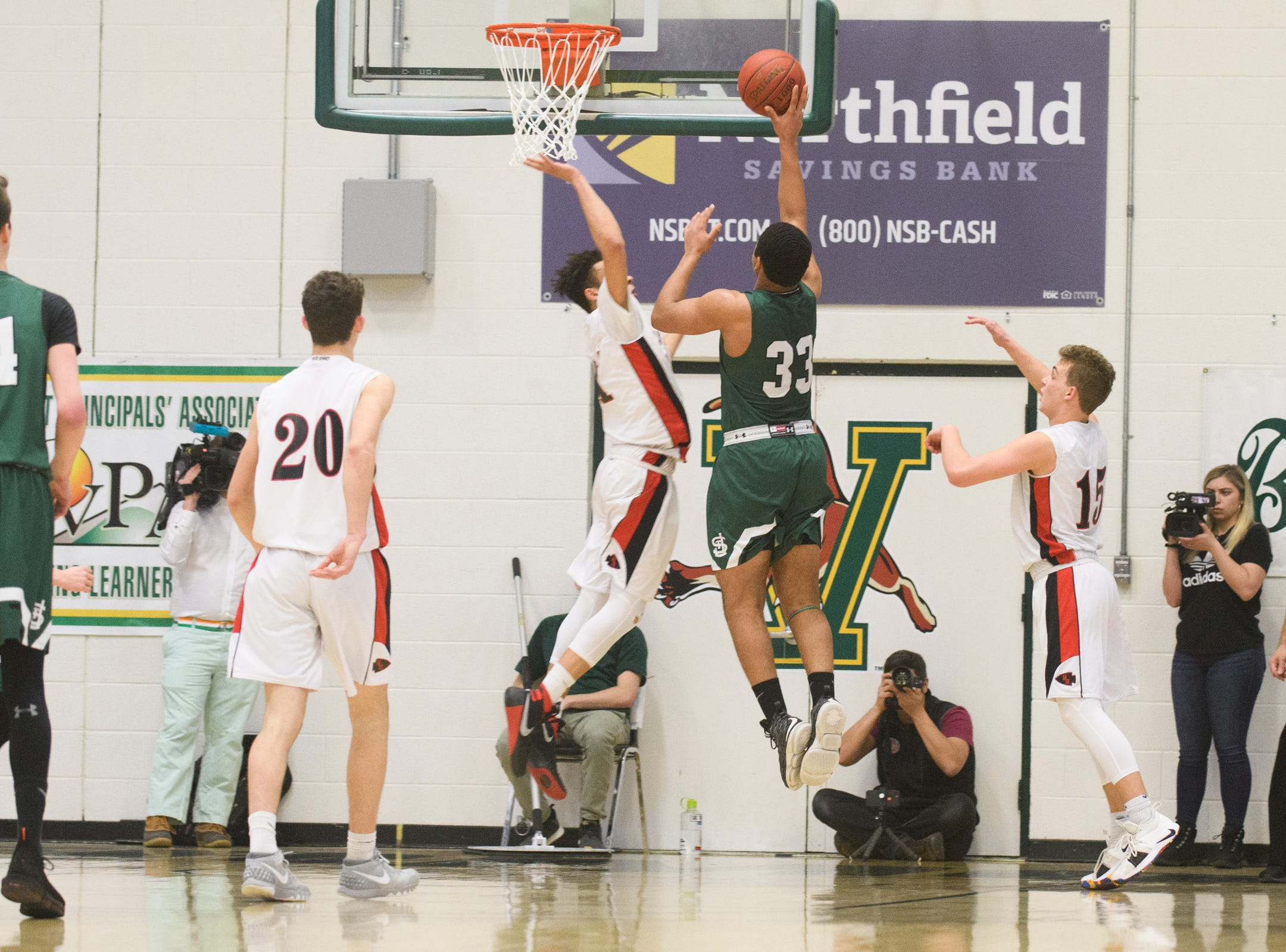 St. Johnsbury's Asom Hayman-Jones (34) leaps for a lay up over Rutland's Jamison Evans (21) during the DI boys basketball championship game between the St. Johnsbury Hilltoppers and the Rutland Raiders at Patrick Gym on Sunday afternoon March 17, 2019 in Burlington, Vermont.