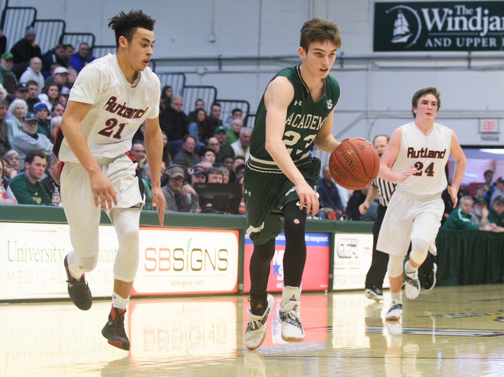 St. Johnsbury's Logan Wendell (23) drives to the hoop past Rutland's Jamison Evans (21) during the DI boys basketball championship game between the St. Johnsbury Hilltoppers and the Rutland Raiders at Patrick Gym on Sunday afternoon March 17, 2019 in Burlington, Vermont.