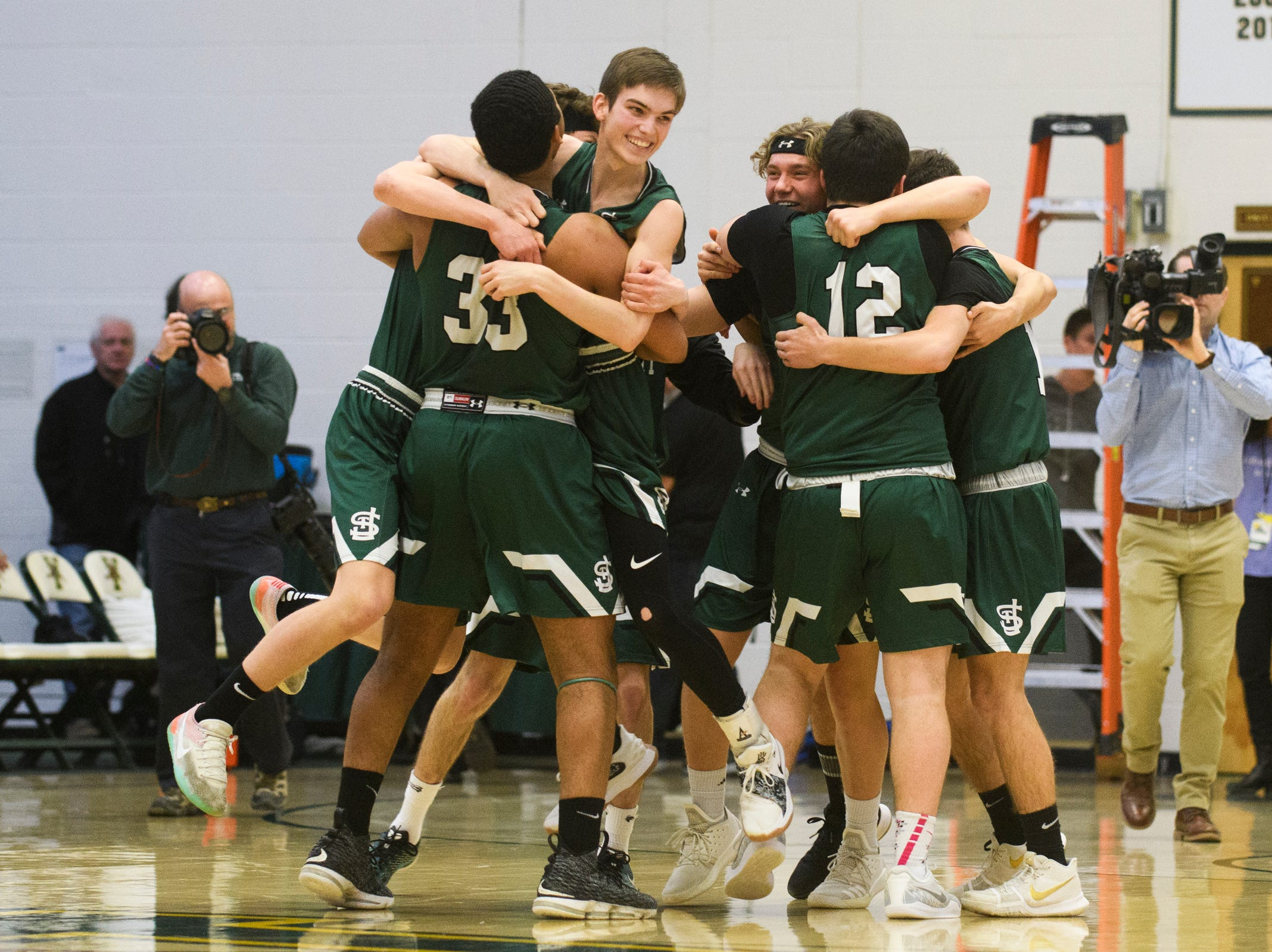 St. Johnsbury celebrates the championship during the DI boys basketball championship game between the St. Johnsbury Hilltoppers and the Rutland Raiders at Patrick Gym on Sunday afternoon March 17, 2019 in Burlington, Vermont.