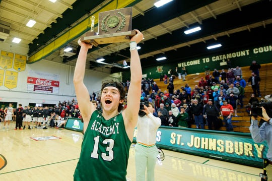 St. Johnsbury's Alex Carlisle (13) celebrates with the championship trophy during the DI boys basketball championship game between the St. Johnsbury Hilltoppers and the Rutland Raiders at Patrick Gym on Sunday afternoon March 17, 2019 in Burlington, Vermont.