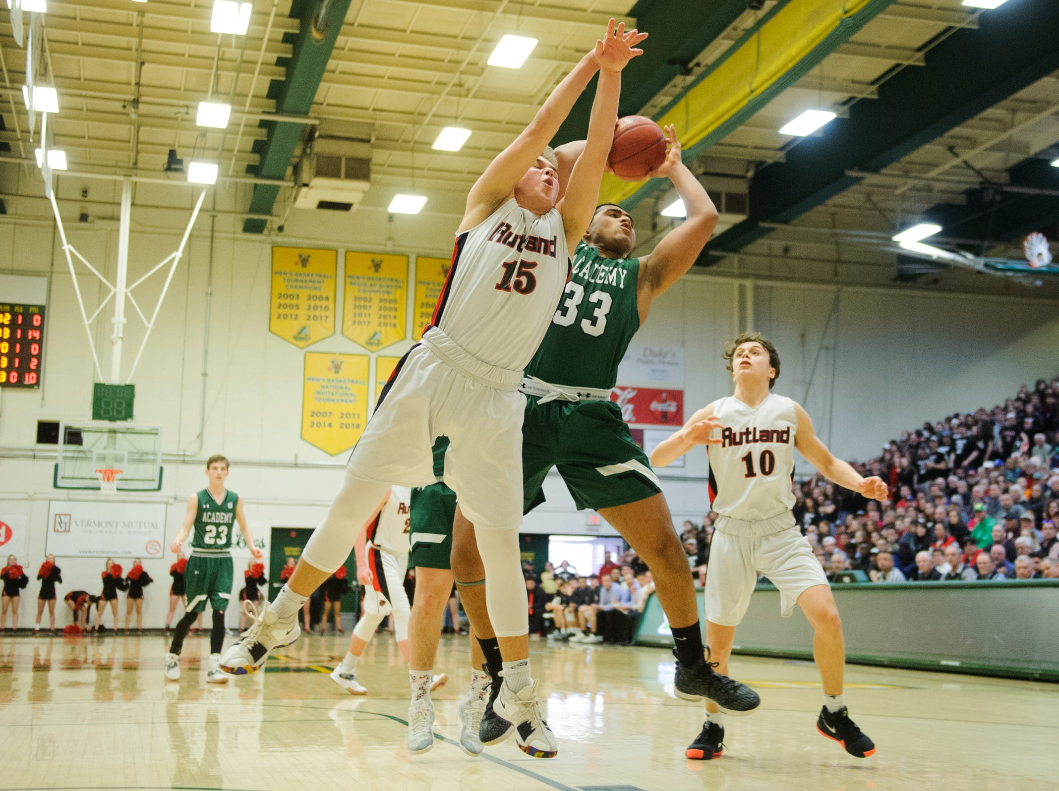 St. Johnsbury's Asom Hayman-Jones (34) and Rutland's Jacob Lorman (24 battle for the rebound during the DI boys basketball championship game between the St. Johnsbury Hilltoppers and the Rutland Raiders at Patrick Gym on Sunday afternoon March 17, 2019 in Burlington, Vermont.
